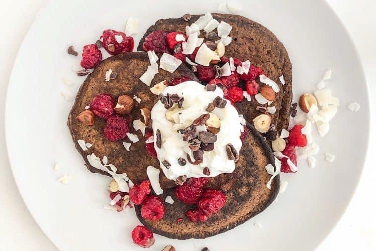 Koolhydraatarme chocolade pannenkoeken met frambozen en slagroom.