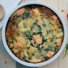 Quiche met zalm, spinazie en geraspte kaas.