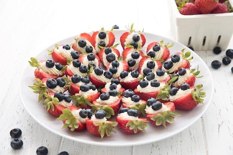 Aardbeien met cheesecake-vulling en blauwe bessen.