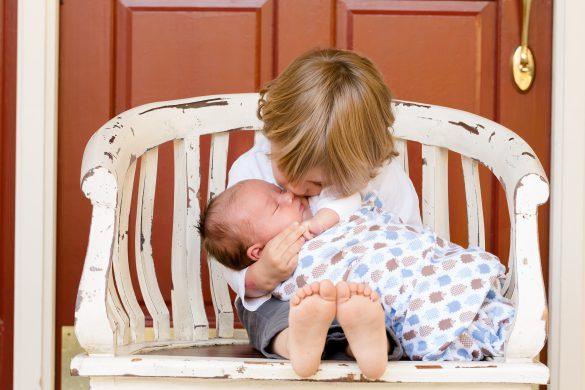 Kleiner Junge hält Baby im Arm