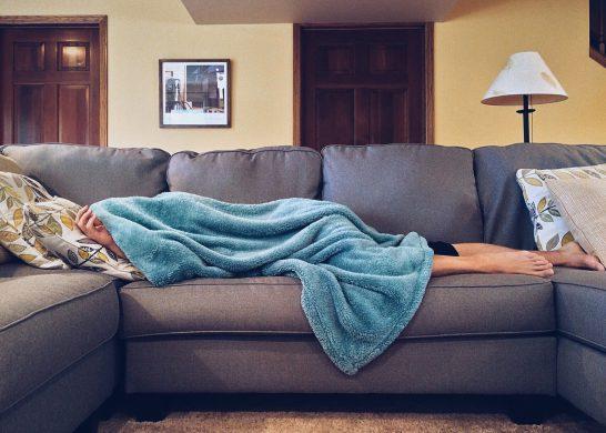 Frau auf Sofa mit Decke über dem Kopf