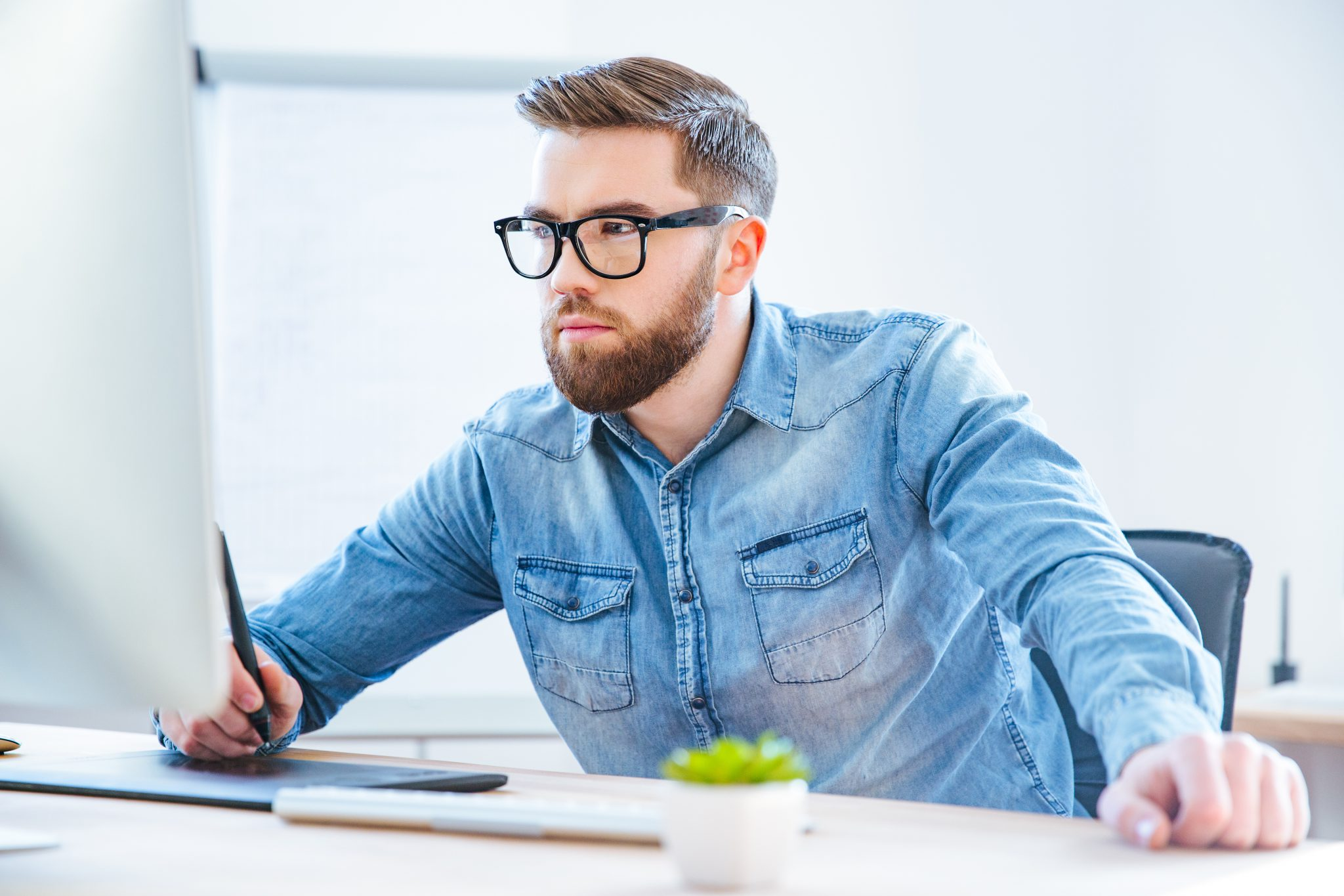 Serious concentrated man designer drawing with graphic pen tablet