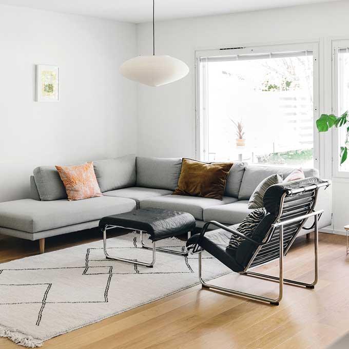 Kuvassa Tiina Hautalan olohuone ja Hakolan Lazy-kulmadivaani vaaleanharmaalla Florist-kankaalla.