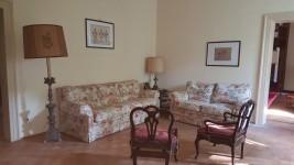 Cornice, mobile scantonato, abatjour, sedie, divani, tavolino, lampada, ...