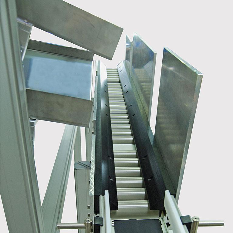 Kunststoffteile fallen über eine Rampe auf die Rollenbahn. - Plastic parts fall onto the roller conveyor via a ramp.