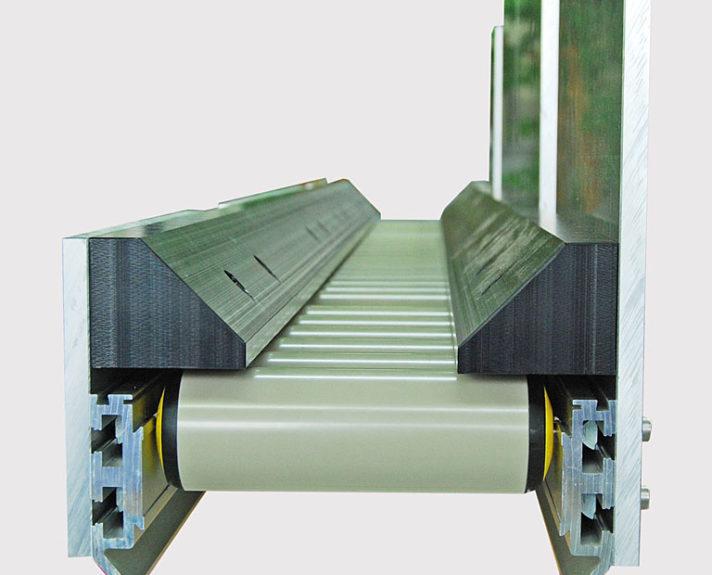 Die Kunststoffteile auf der Rollenbahn werden zentriert. - The plastic parts on the roller conveyor are thereby centered.