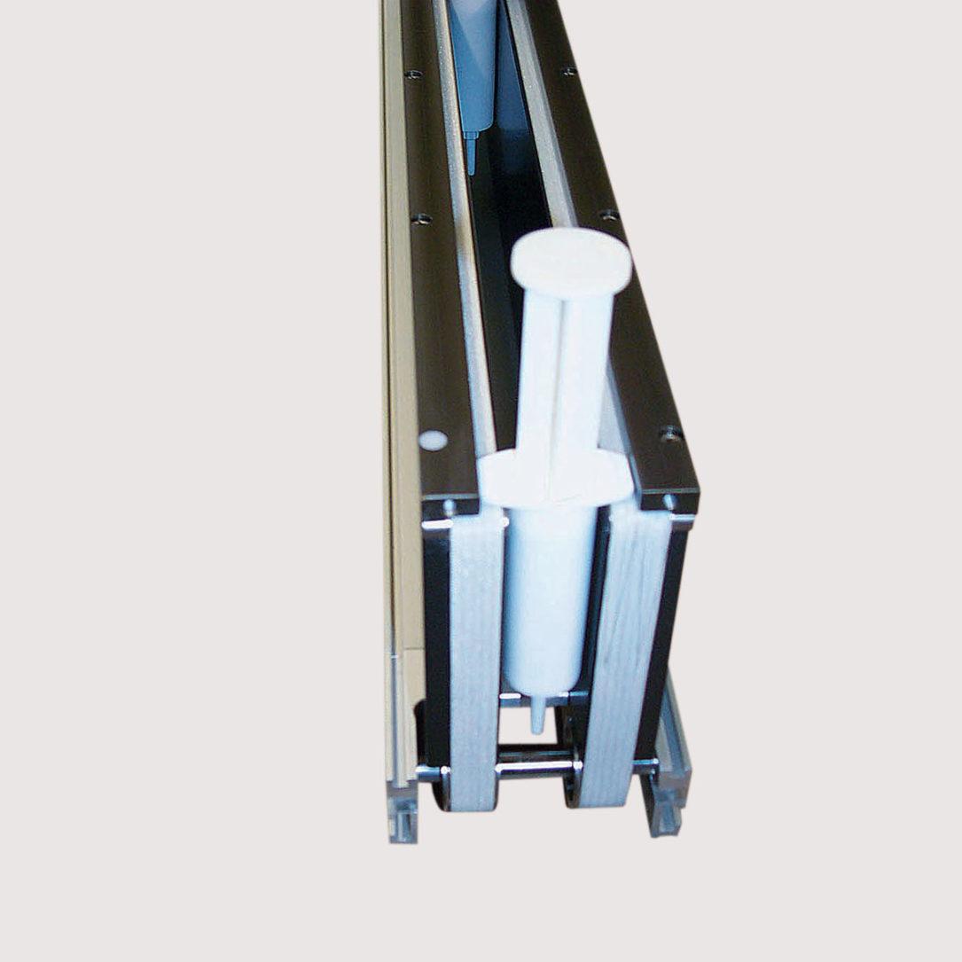 Spritzentransport mit beidseitiger Gurtunterlage. - Transport of syringes with belt underlay.