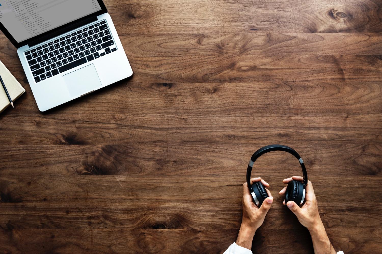 Männerhände halten Kopfhörer. Dahinter sieht man die Arbeitsplatte eines Schreibtischs. Darauf steht ein Macbook. Foto: rawpixel.com/Unsplash