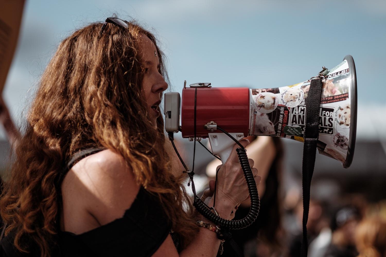 Frau spricht in Megafon. Im übertragenen Sinne sollten wir das nicht tun - marktschreien, wenn wir kein Marktschreier sind. Foto: Clem Onojeghuo / Unsplash
