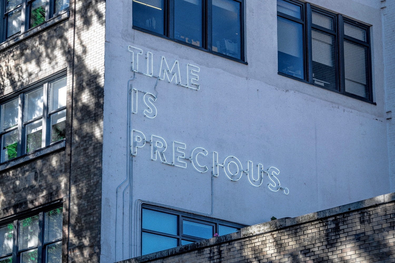 """Neon-Schriftzug """"Time is Precious"""" an Gebäudewand. Foto: Joe Hu/Unsplash"""
