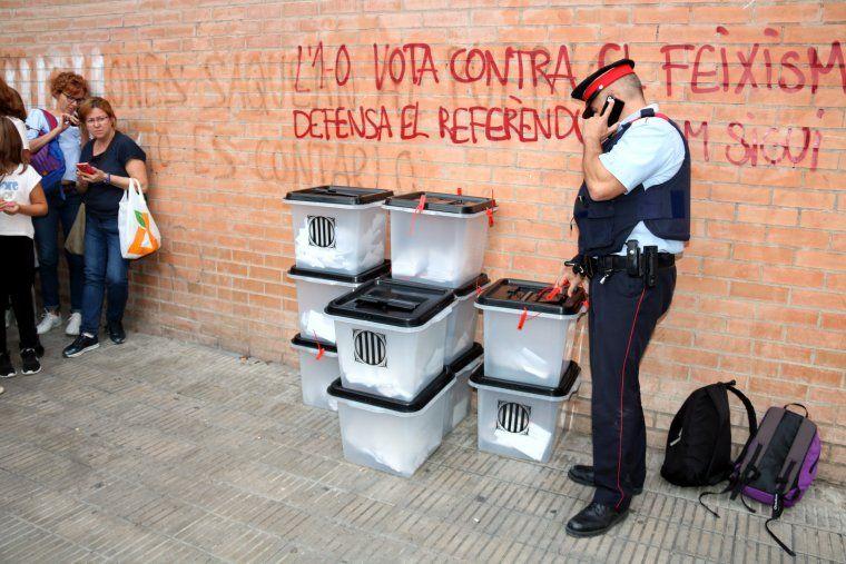 Un agent dels Mossos d'Esquadra inspeccionant les deu urnes amb què es va votar l'1-O a l'institut Josep Lladonosa de Lleida