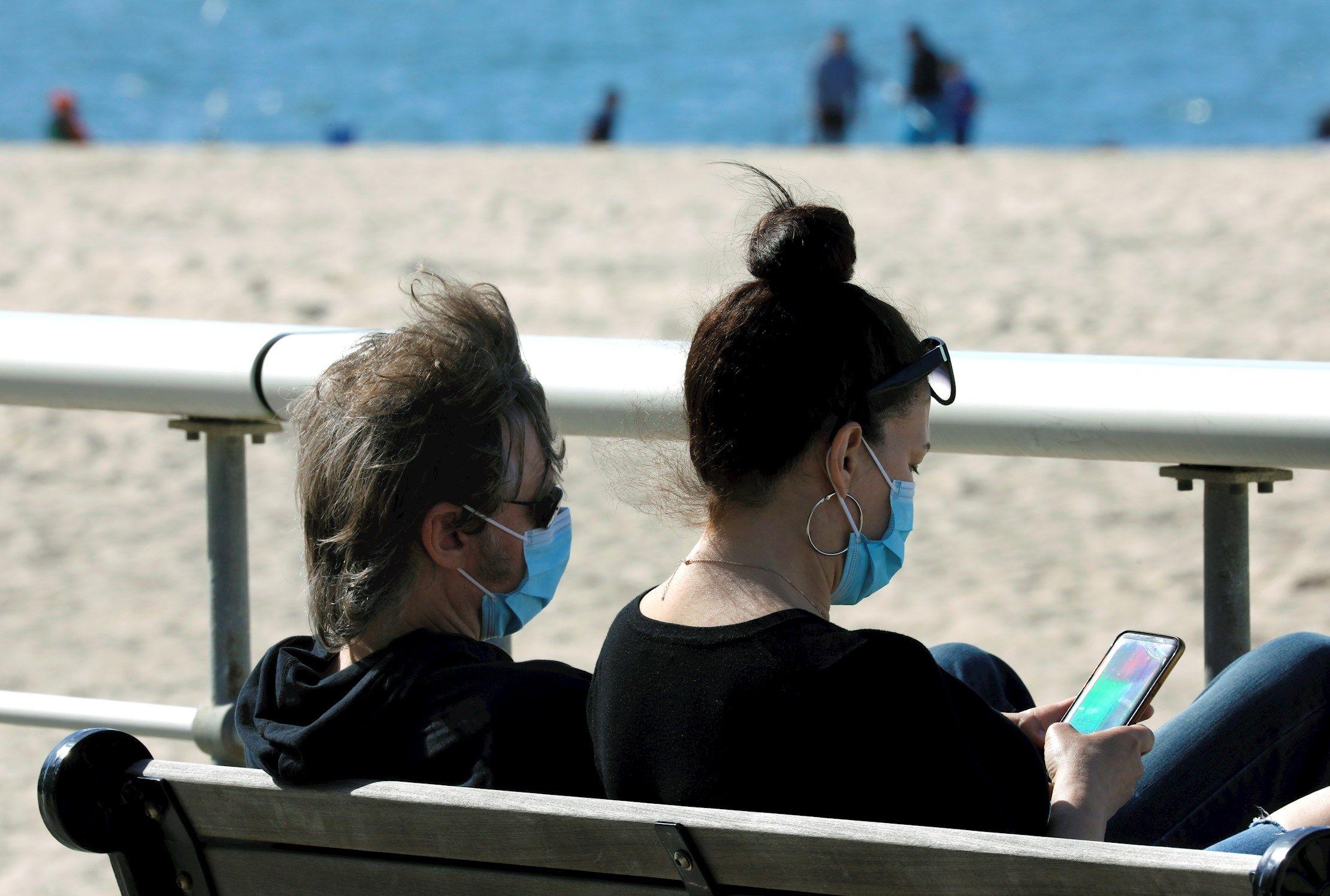Dues persones amb mascareta assegudes en un banc davant del mar