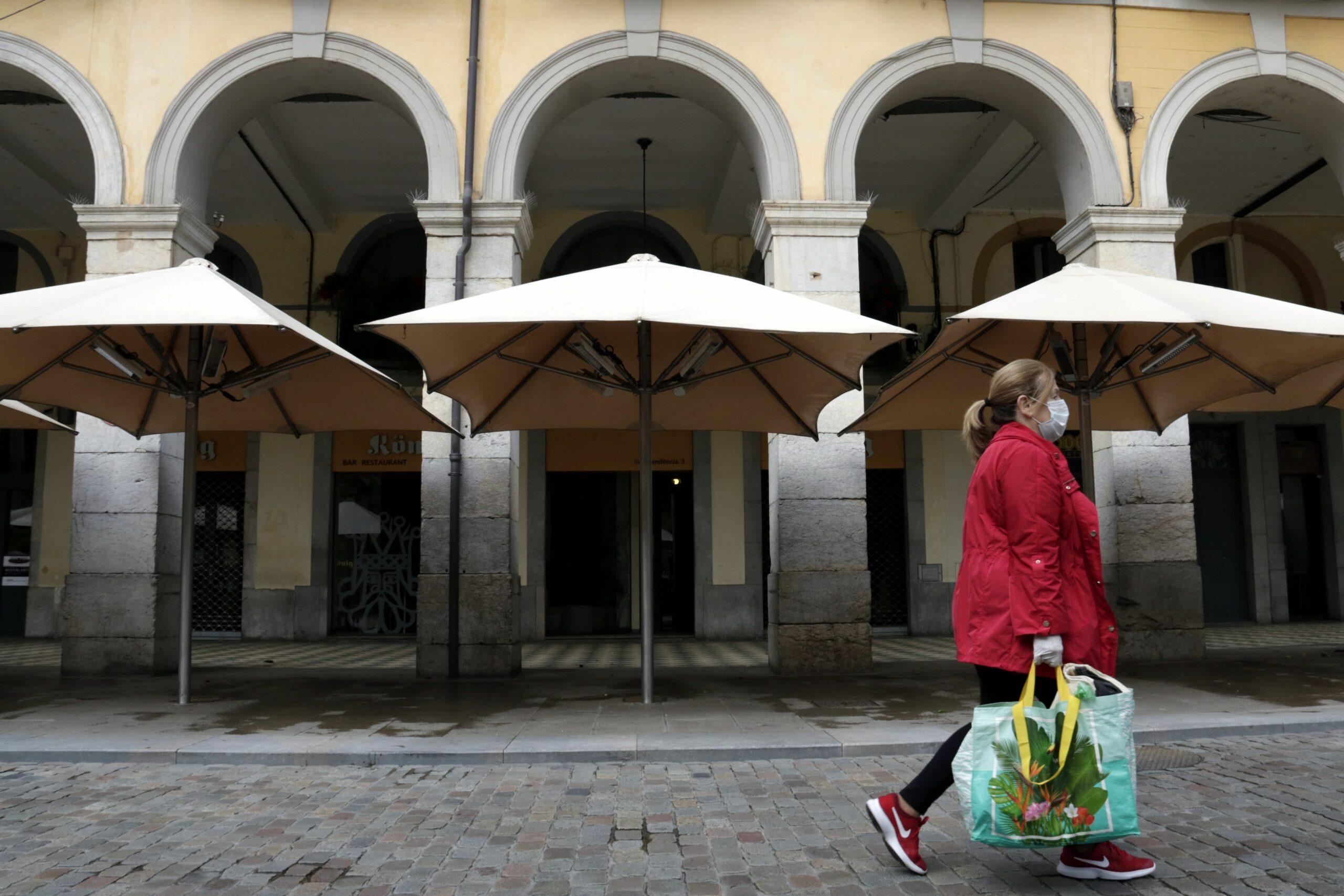 Una dona amb mascareta passa per davant de les terrasses buides i els restaurants tancats a la plaça Independència de Girona