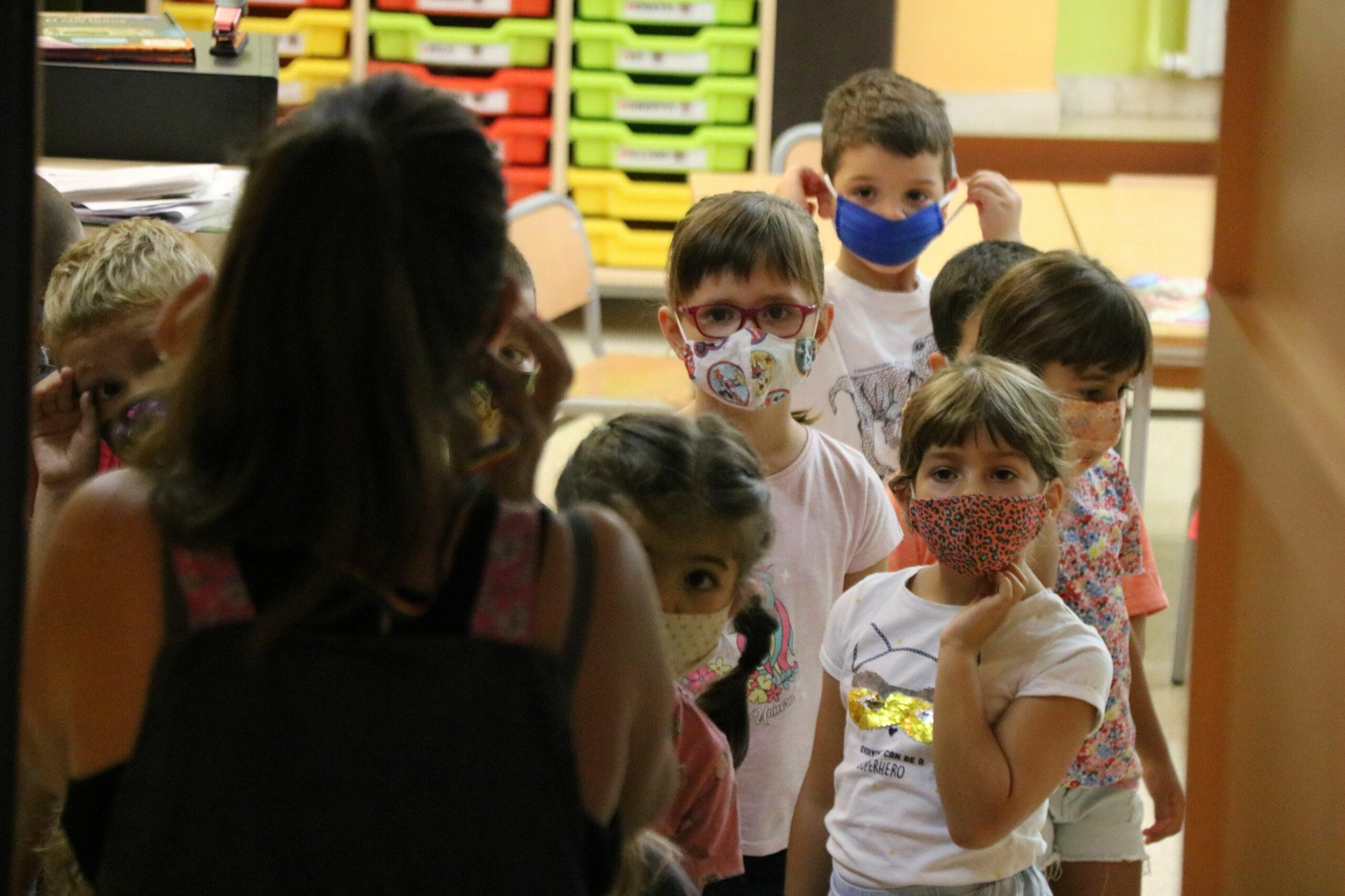 Un grup d'alumnes sortint de la seva classe amb les mascaretes posades a l'Escola Catal?nia de Barcelona