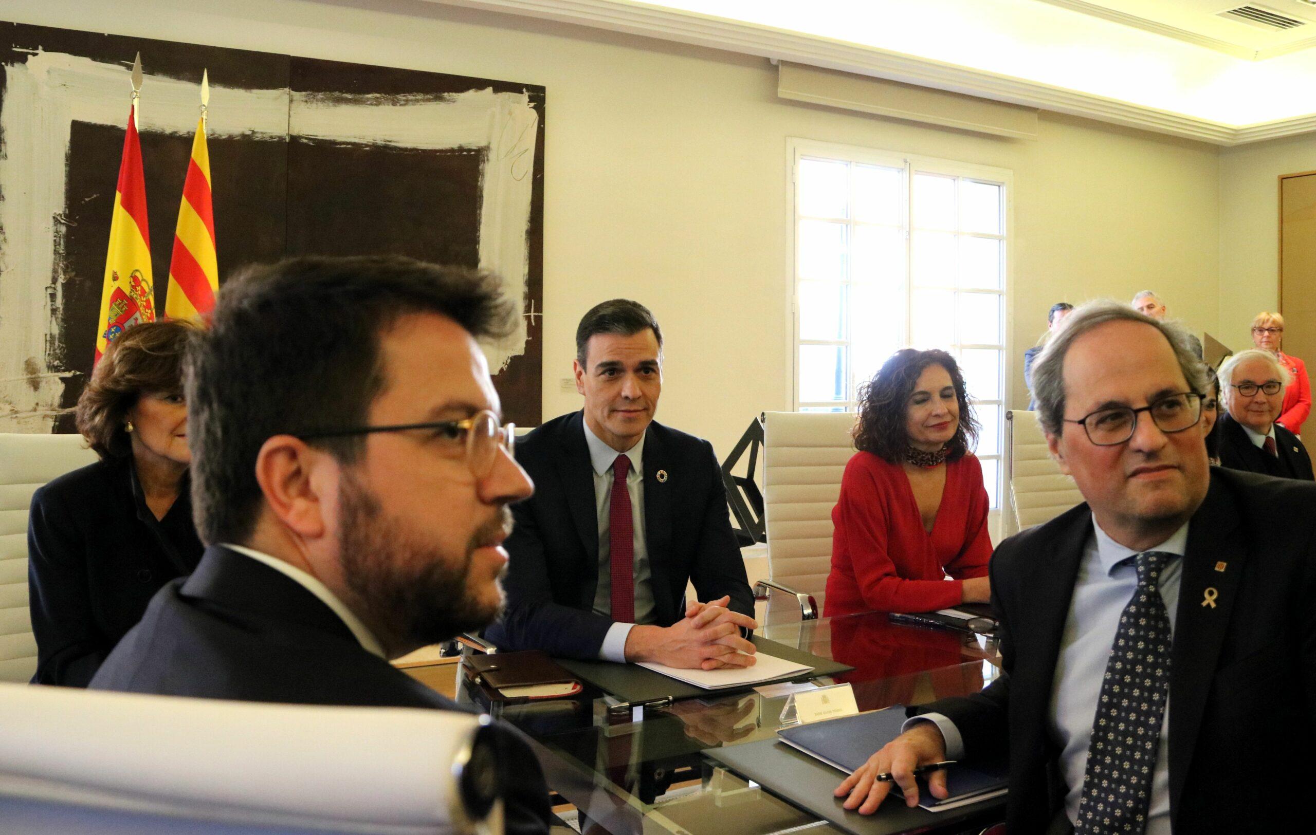 Pere Aragonés i Quim Torra en primer terme amb Pedro Sánchez al darrere a la mesa de diàleg