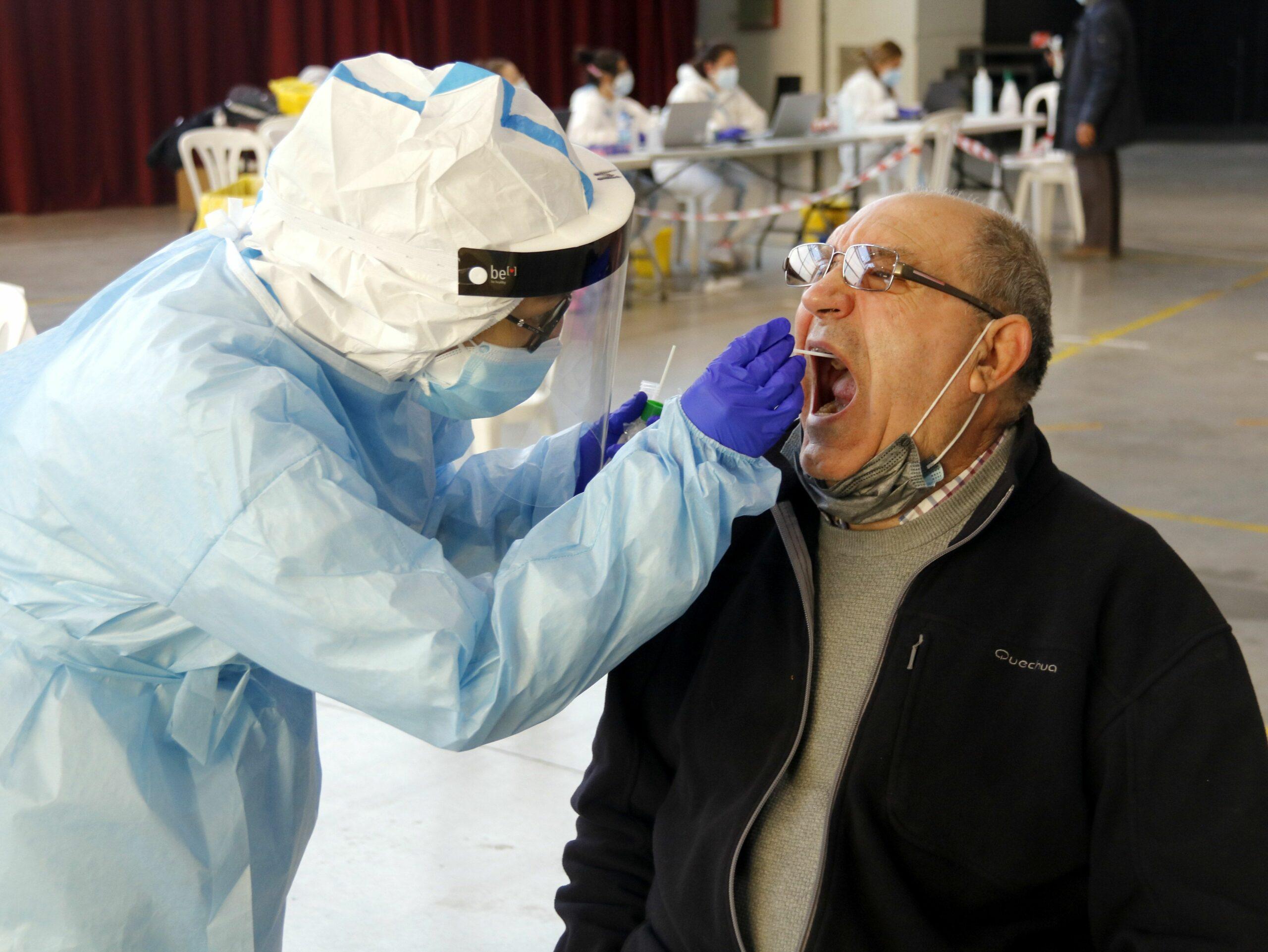 Imatge d'arxiu d'un home fent-se la prova PCR amb un tècnic sanitari al pavelló de l'Oli de les Borges Blanques