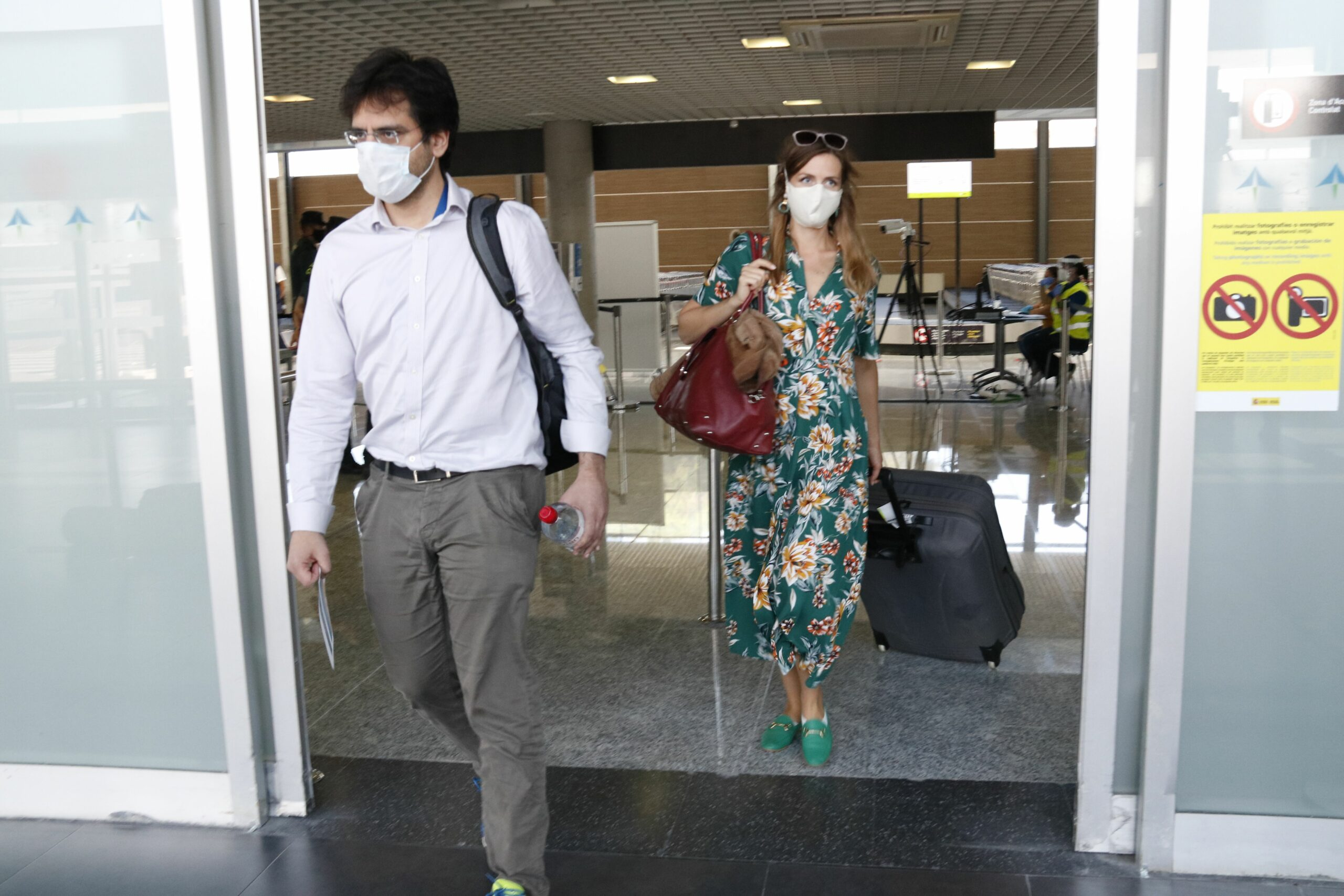 Pla obert de dos passatgers amb mascareta, sortint del control de temperatura, a la terminal d'arribades de l'aeroport de Reus,
