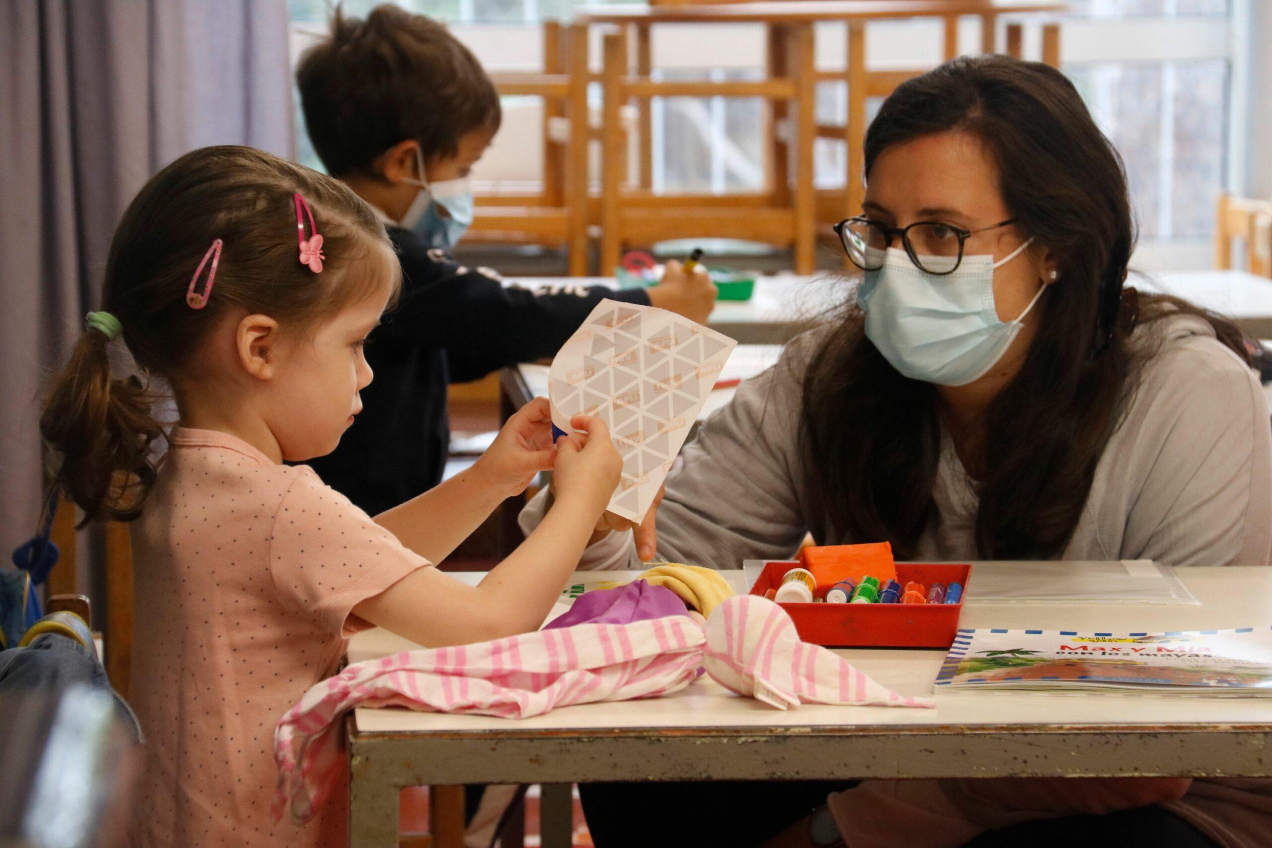 Una mestra interacciona amb una alumna d'infantil a l'Institut Escola Costa i Llobera