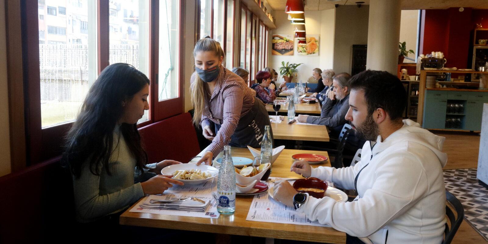 Una cambrera serveix un dinar a una parella al restaurant 'El racó' de la plaça Independència de Girona | ACN