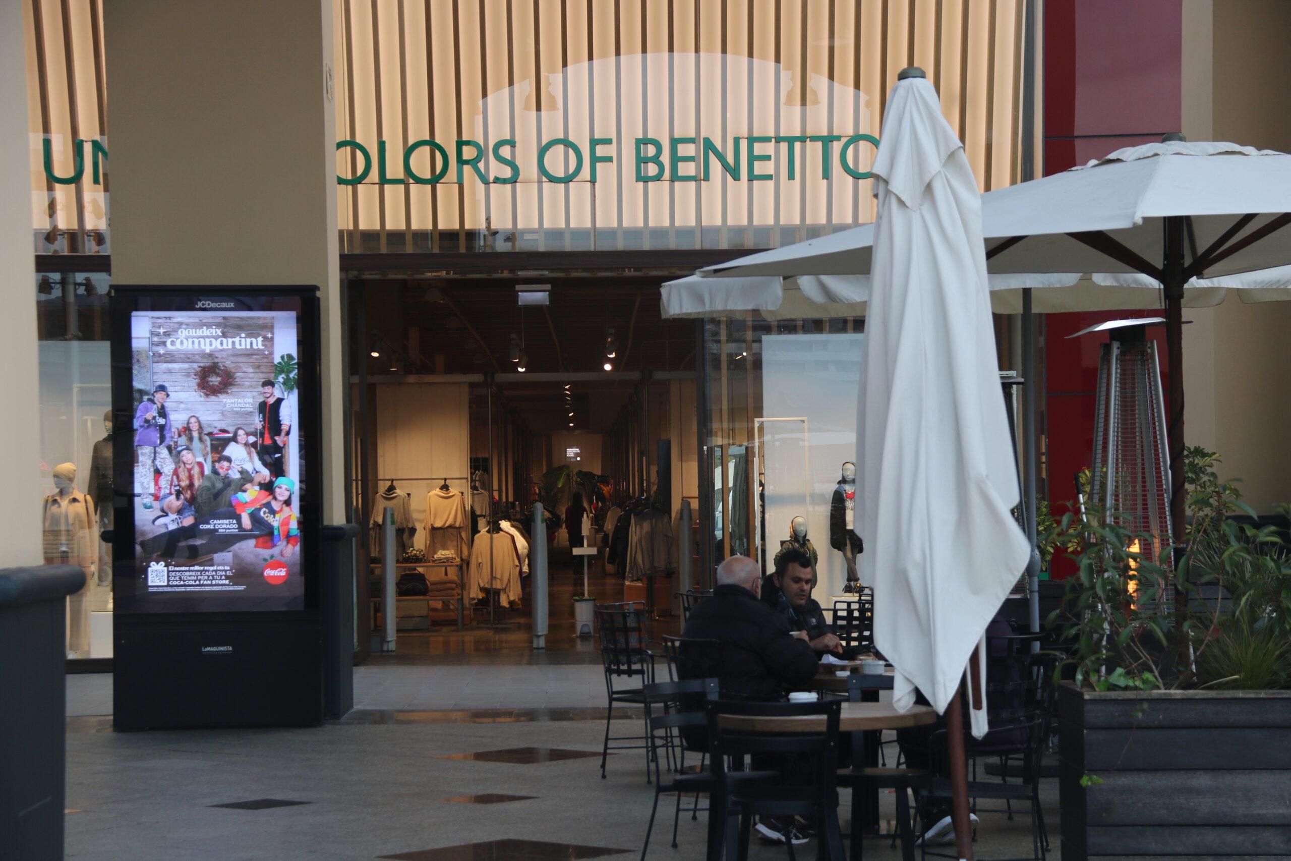 Dues persones prenent un cafè a una terrassa dins el centre comercial La Maquinista, davant una botiga de roba, durant el primer dia de reobertura del centres. Imatge del 14 de desembre de 2020 / ACN