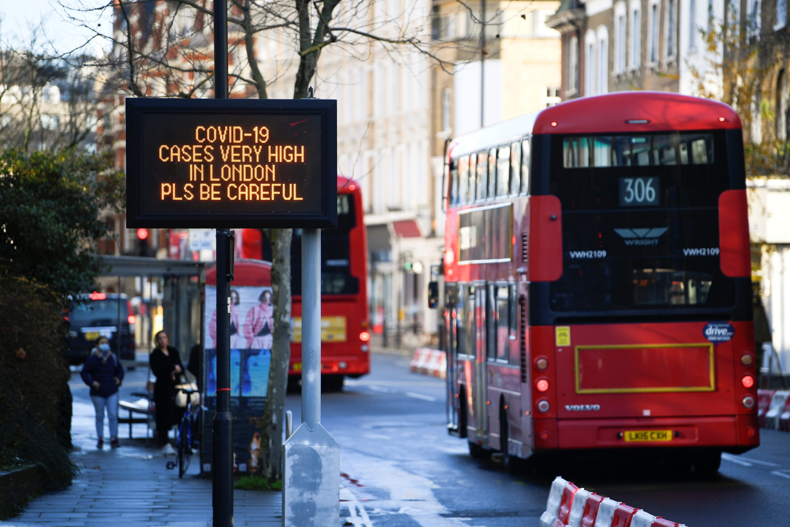 Busses pass a sign with a public health information message, amid the spread of the coronavirus disease (COVID-19), as new restrictions come into force, in London, Britain, December 20, 2020. REUTERS/Toby Melville