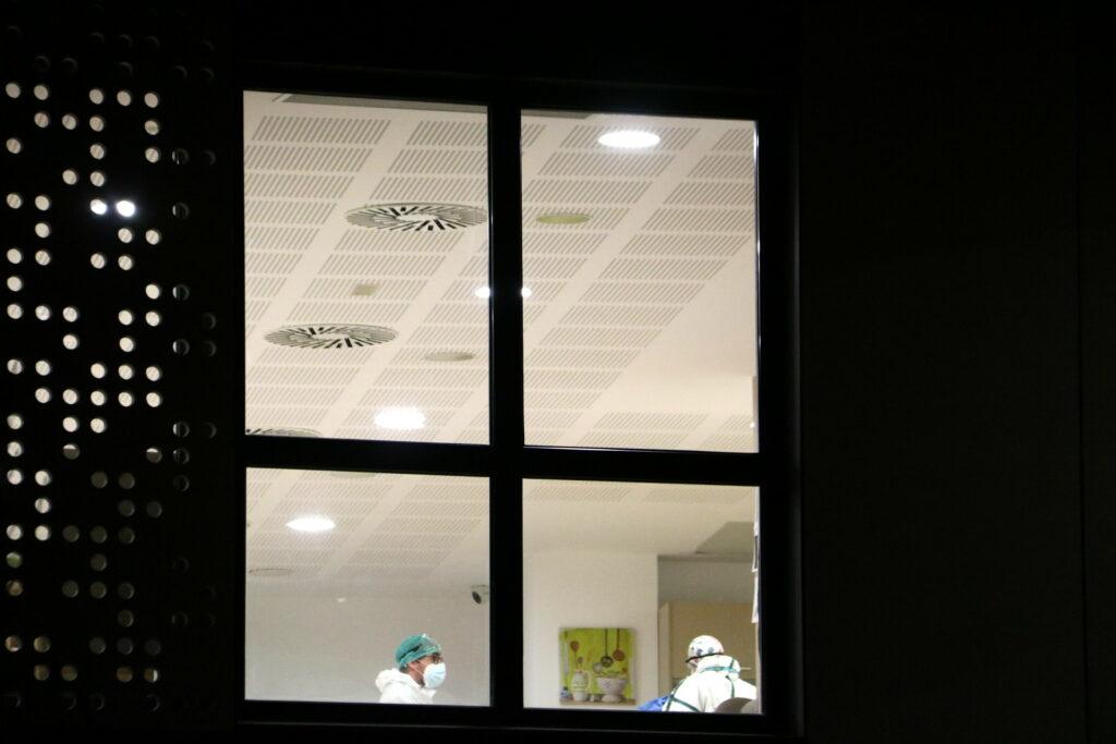 Detall d'una finestra de la residència l'Onada de Santpedor on es veuen dos treballadors a dins. 9 de desembre de 2020 / ACN