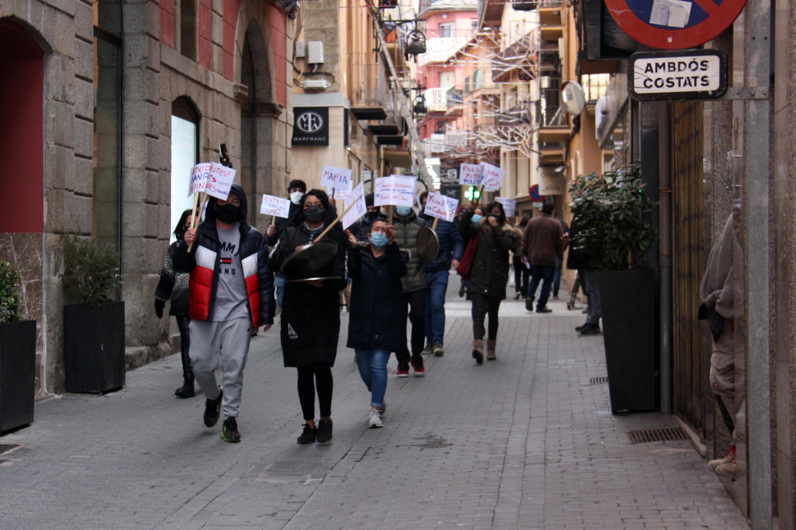 Manifestants del sector de la restauració de la Cerdanya amb pancartes arribant a la concentració convocada a la plaça de l'Ajuntament de Puigcerdà per protestar contra el confinament perimetral | ACN