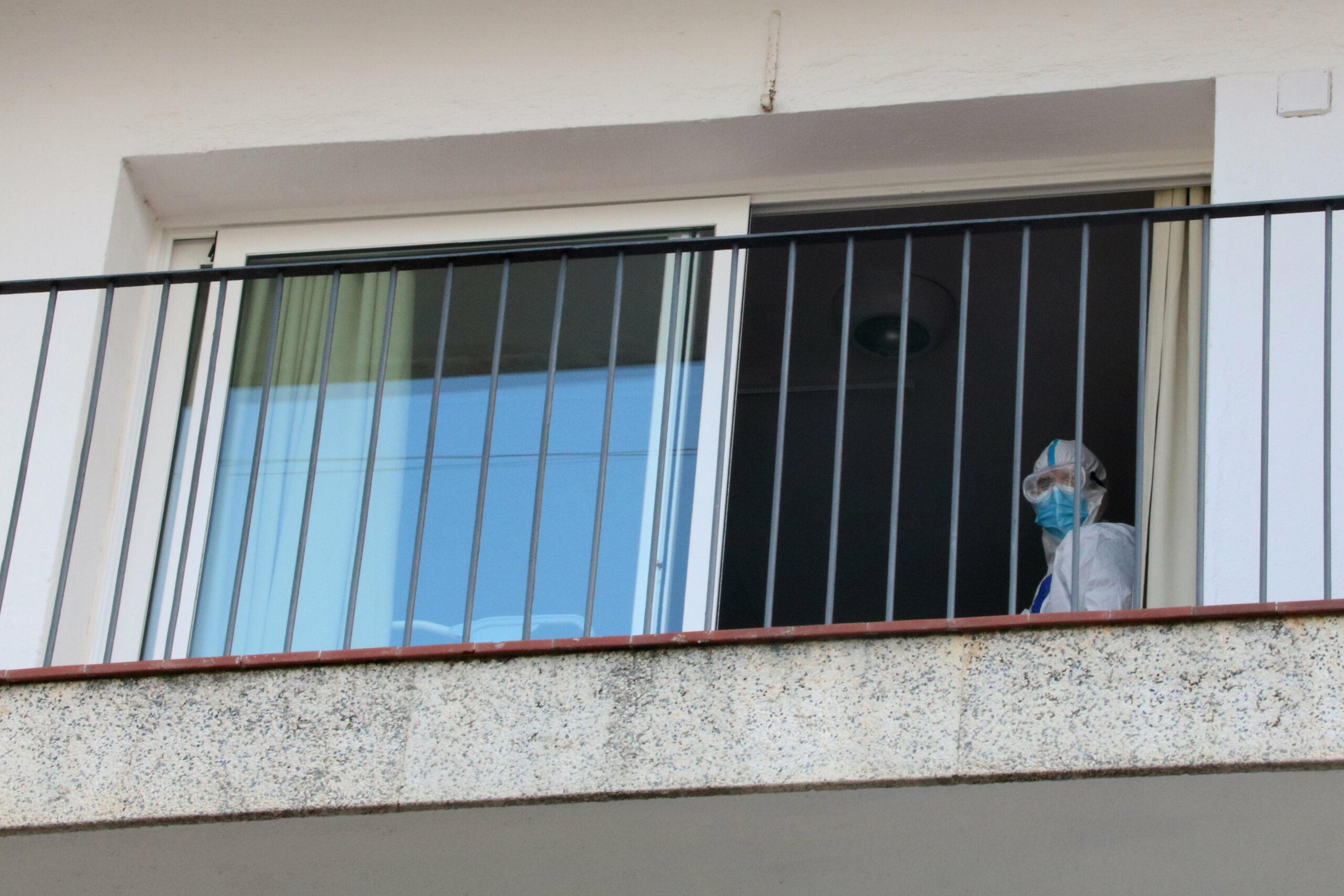 Imatge d'arxiu del balcó d'una habitació de la residència Calafell Park de Segur de Calafell, amb un treballador amb EPI sortint per la porta| ACN