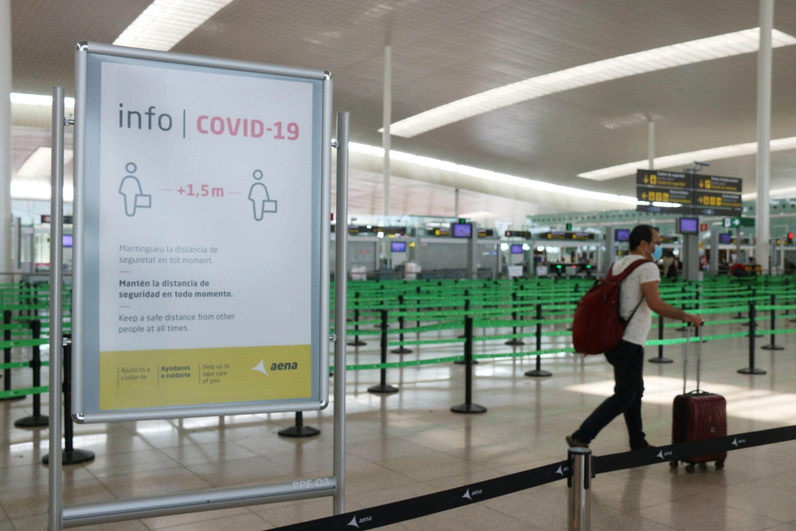 Un cartell informatiu de la covid-19 i d'un passatger arrossegant una maleta amb el control de seguretat de la T1 de l'Aeroport del Prat pràcticament buit, al juliol del 2020 / ACN