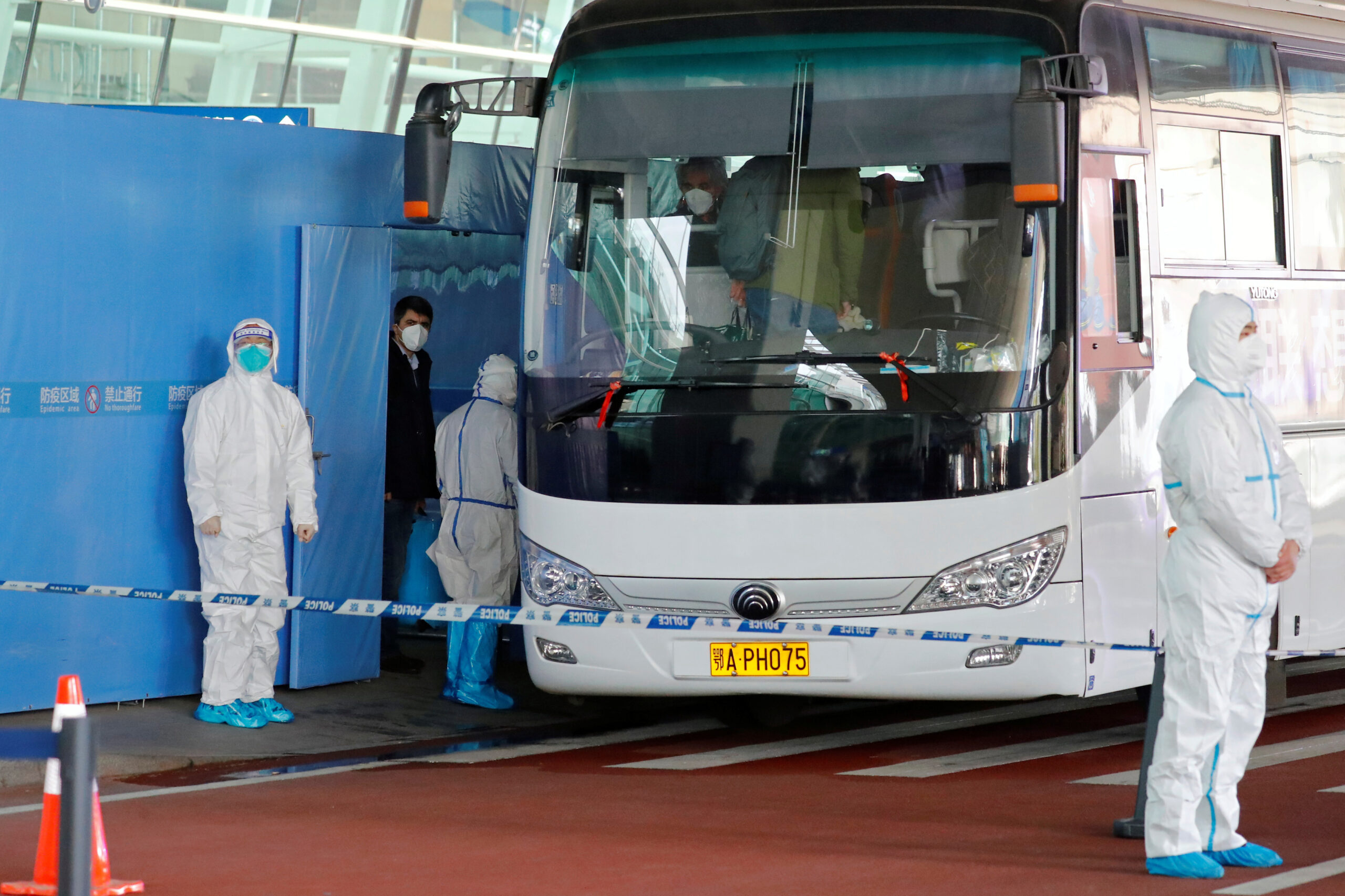 Members of the World Health Organisation (WHO) team tasked with investigating the origins of the coronavirus disease (COVID-19) pandemic board a bus before leaving Wuhan Tianhe International Airport in Wuhan, Hubei province, China January 14, 2021. REUTERS/Thomas Peter