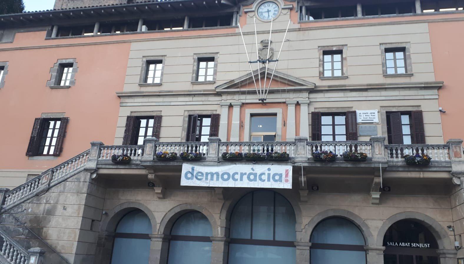 """La pancarta amb la paraula """"democràcia"""" que la junta electoral obliga a retirar de l'Ajuntament de Ripoll / @jordimunell"""