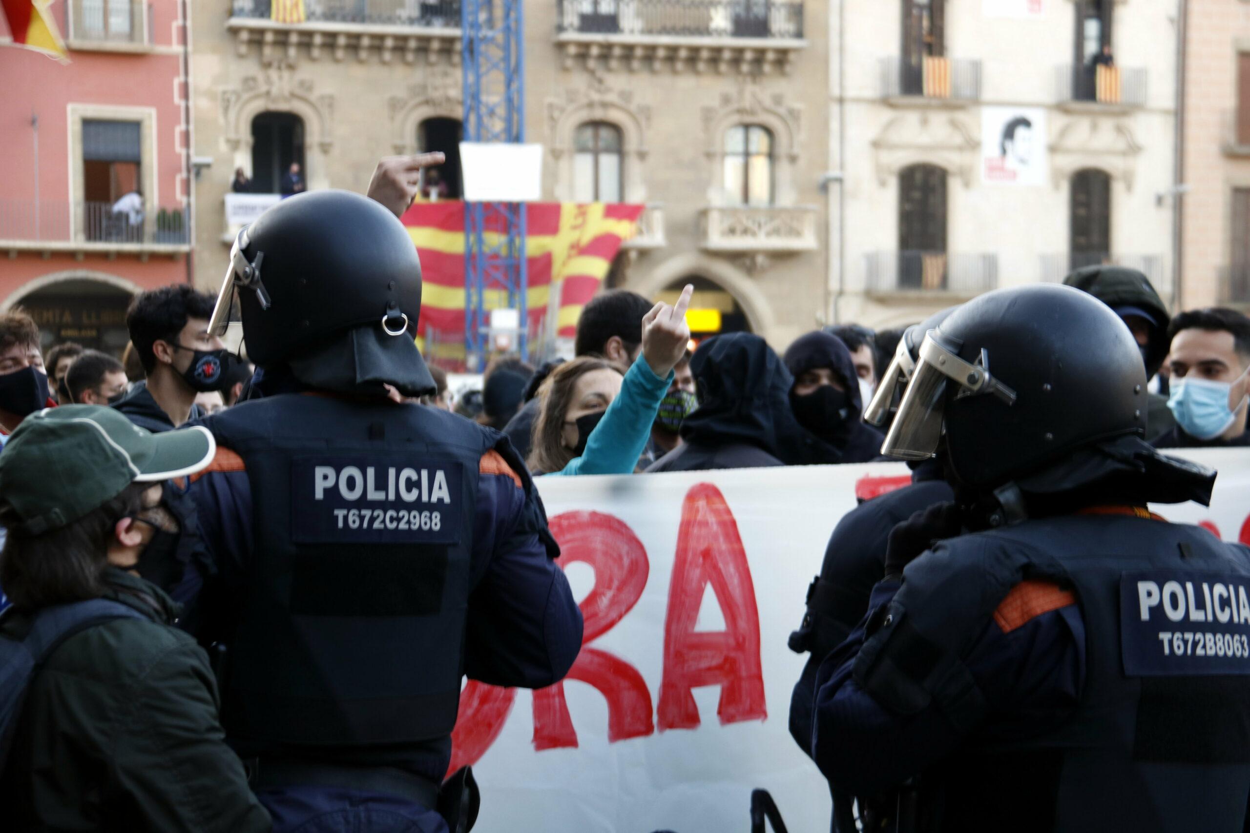 Una manifestant antifeixista, separada per un cordó policial dels Mossos, dels seguidors de Vox, a la plaça Major de Vic el passat dissabte/ACN
