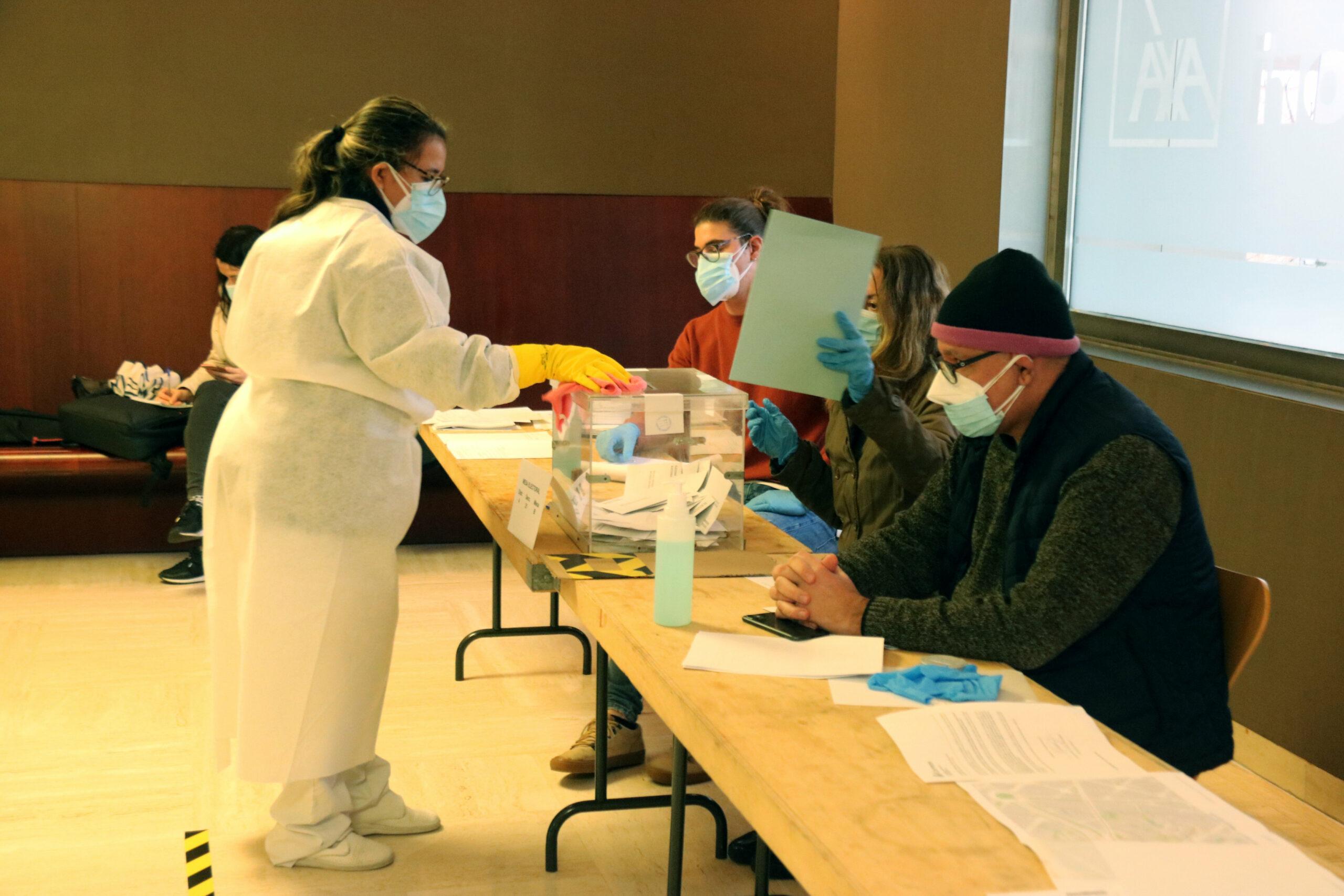 Personal de servei amb equips de protecció individual neteja una urna a l'auditori AXA | ACN
