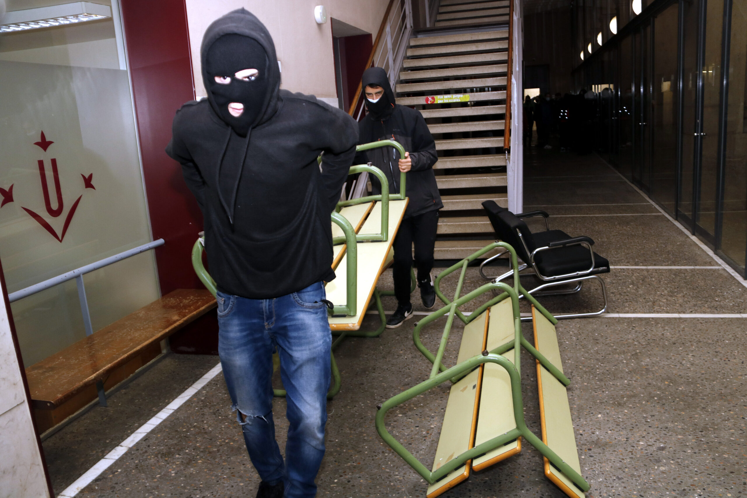 Dos joves encaputxats i amb la cara tapada traslladant un banc per fer barricades i reforçar la tancada a la UdL per Pablo Hasél   ACN