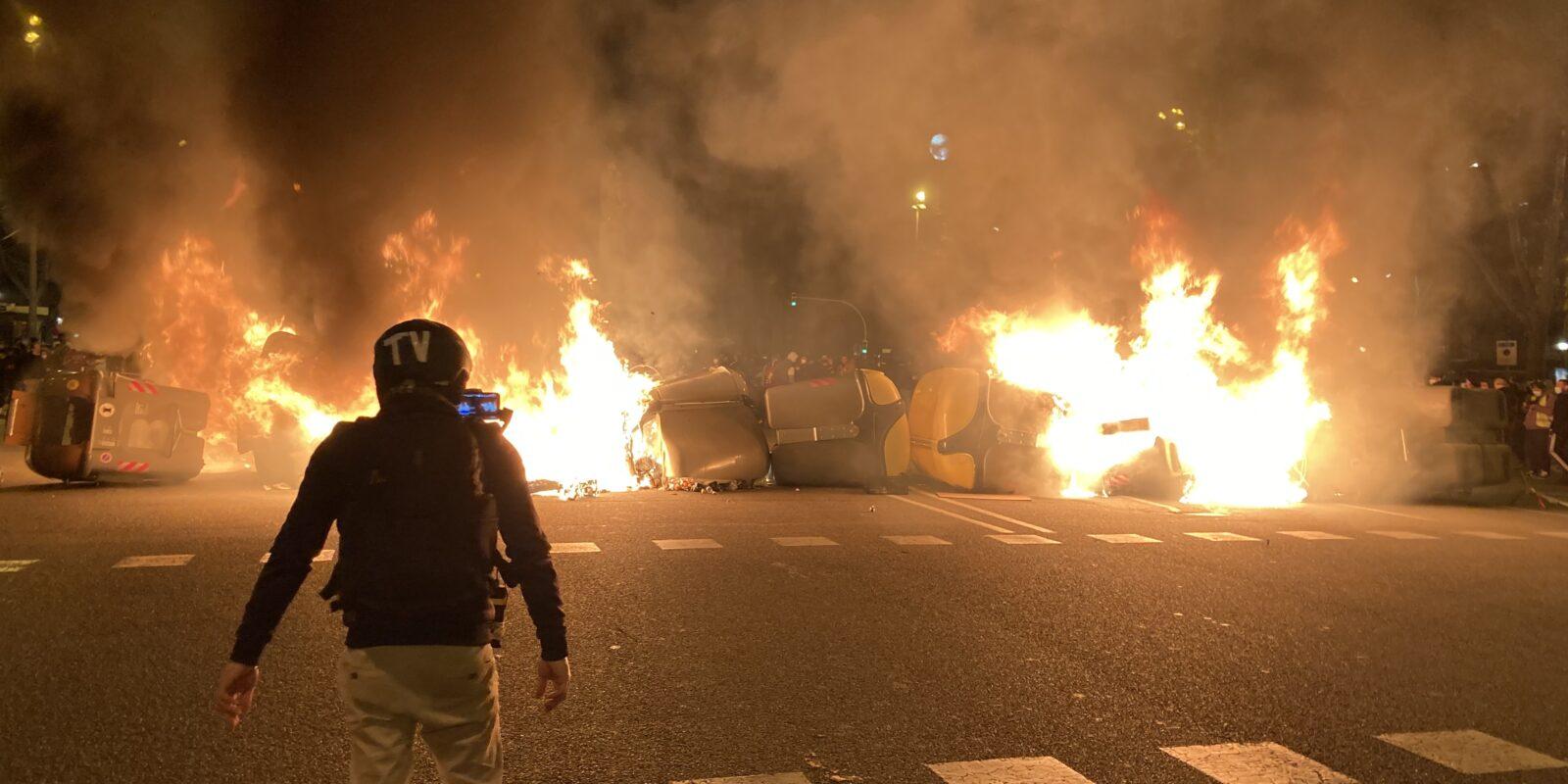 Un manifestant davant d'una barricada de contenidors encesa en la quarta nit de protestes per l'empresonament de Pablo Hasél / ACN