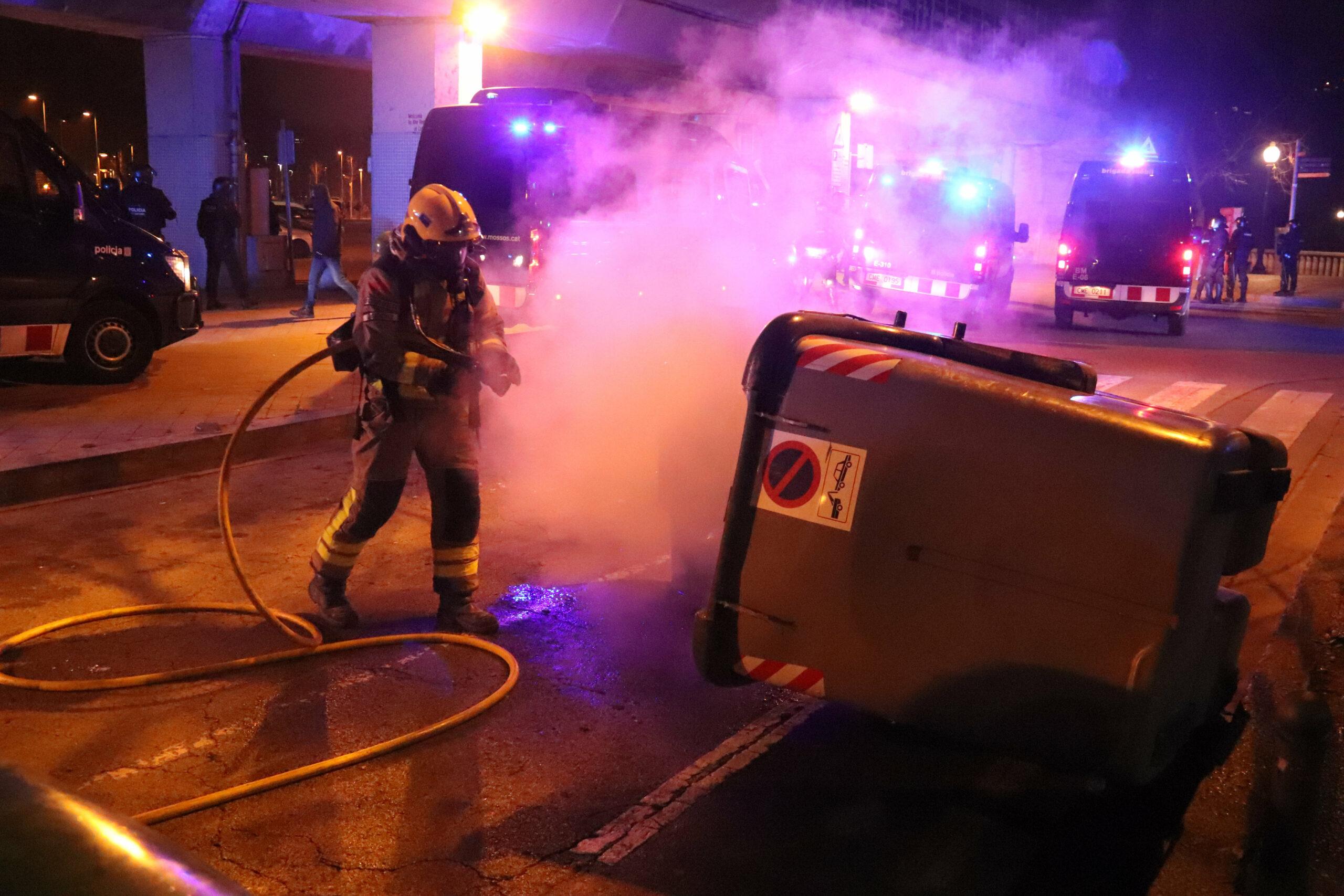 Un bomber apagant un contenidor incendiat al passeig de Canalejas de Girona el 19 de febrer de 2021 / ACN