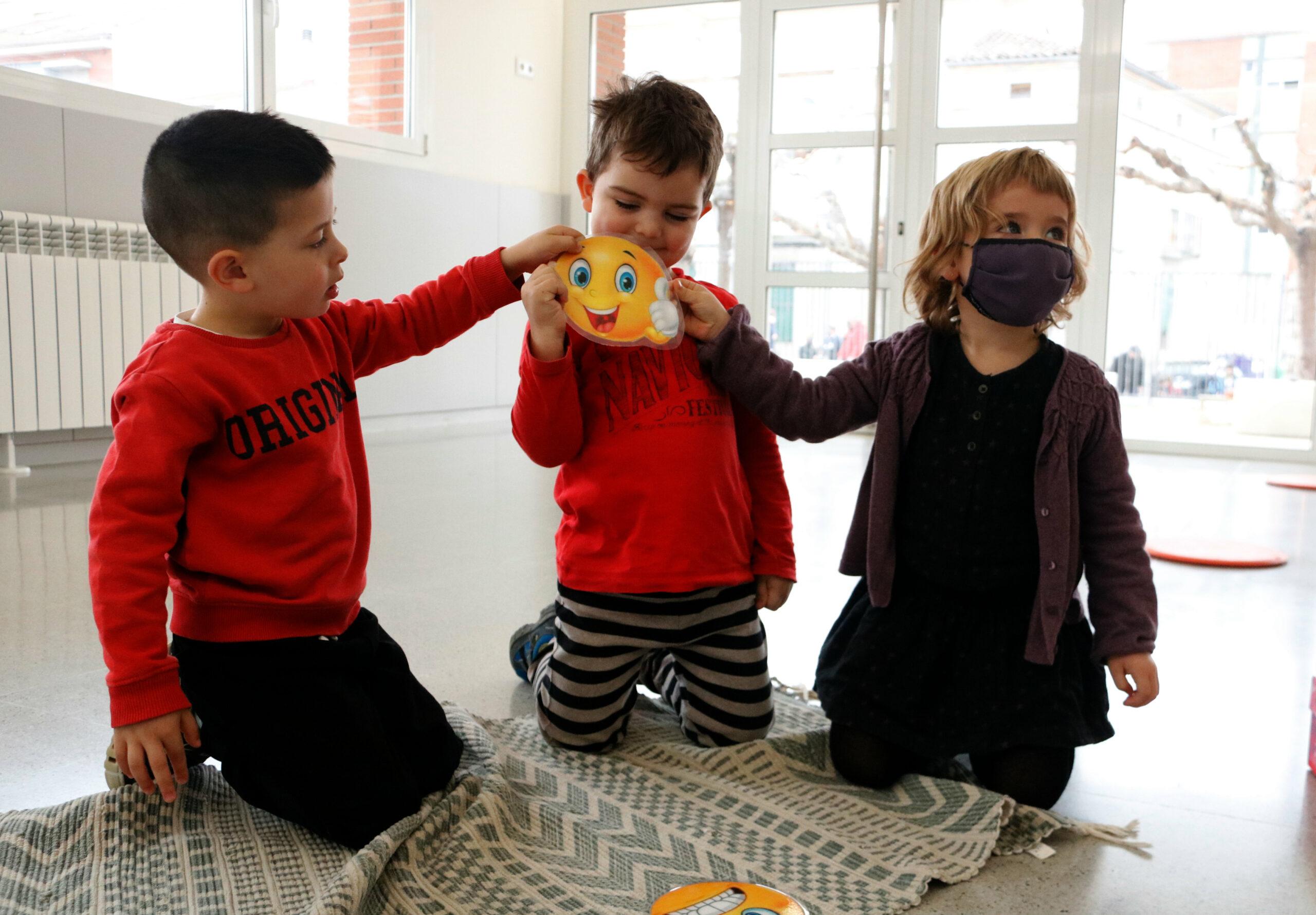 Tres alumnes de P-3 mostrant el seu estat d'ànim a través d'una emoticona | ACN