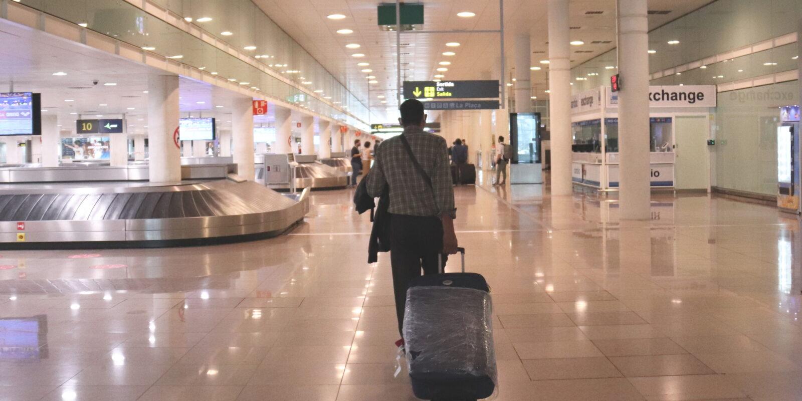 Un viatger caminant amb maletes a la zona d'arribades de la T1 a l'aeroport del Prat el 19 de juny del 2020 / ACN