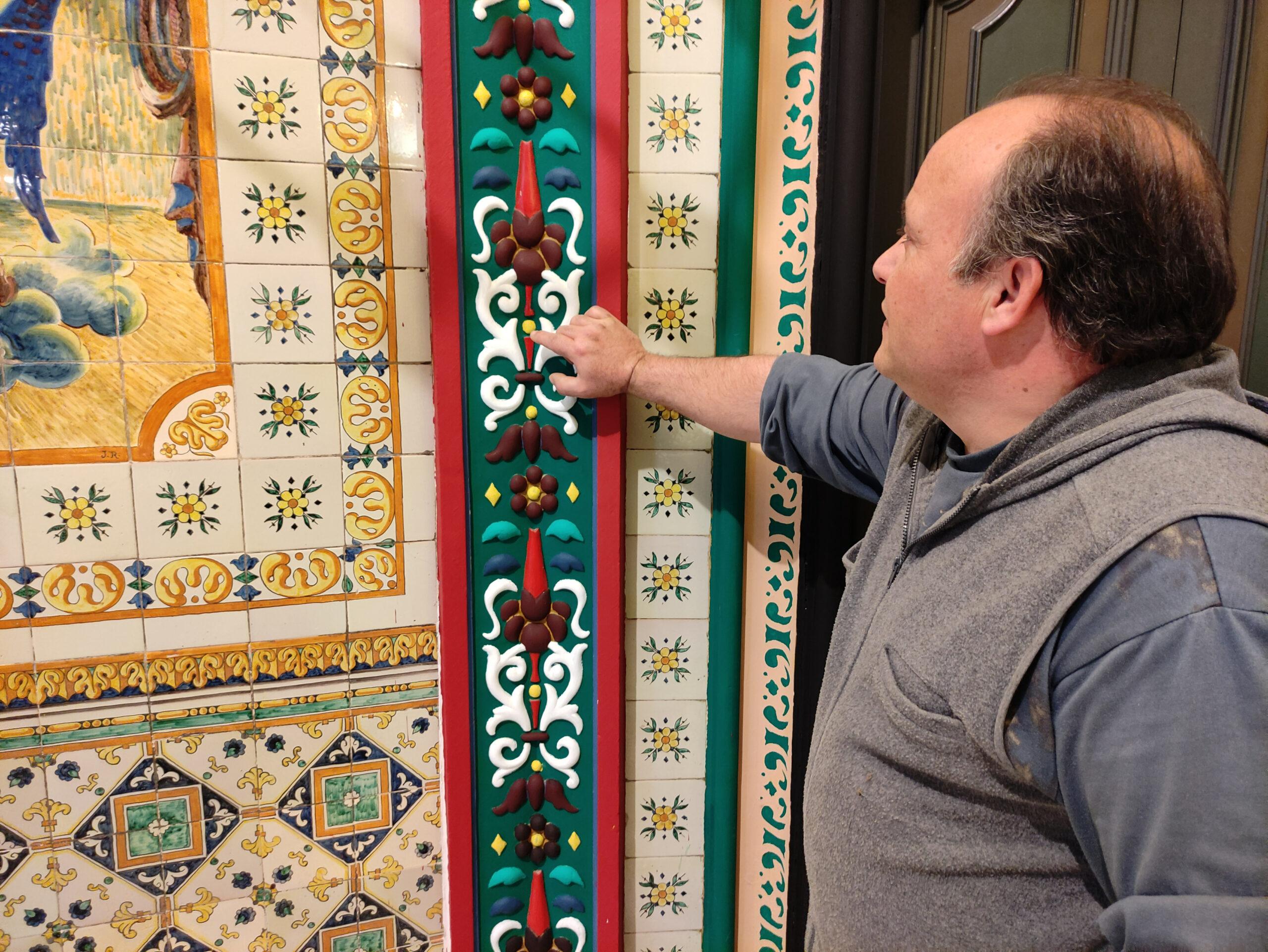 Josep Jiménez mostrant una de les pintures que ha restaurat  (ACN)