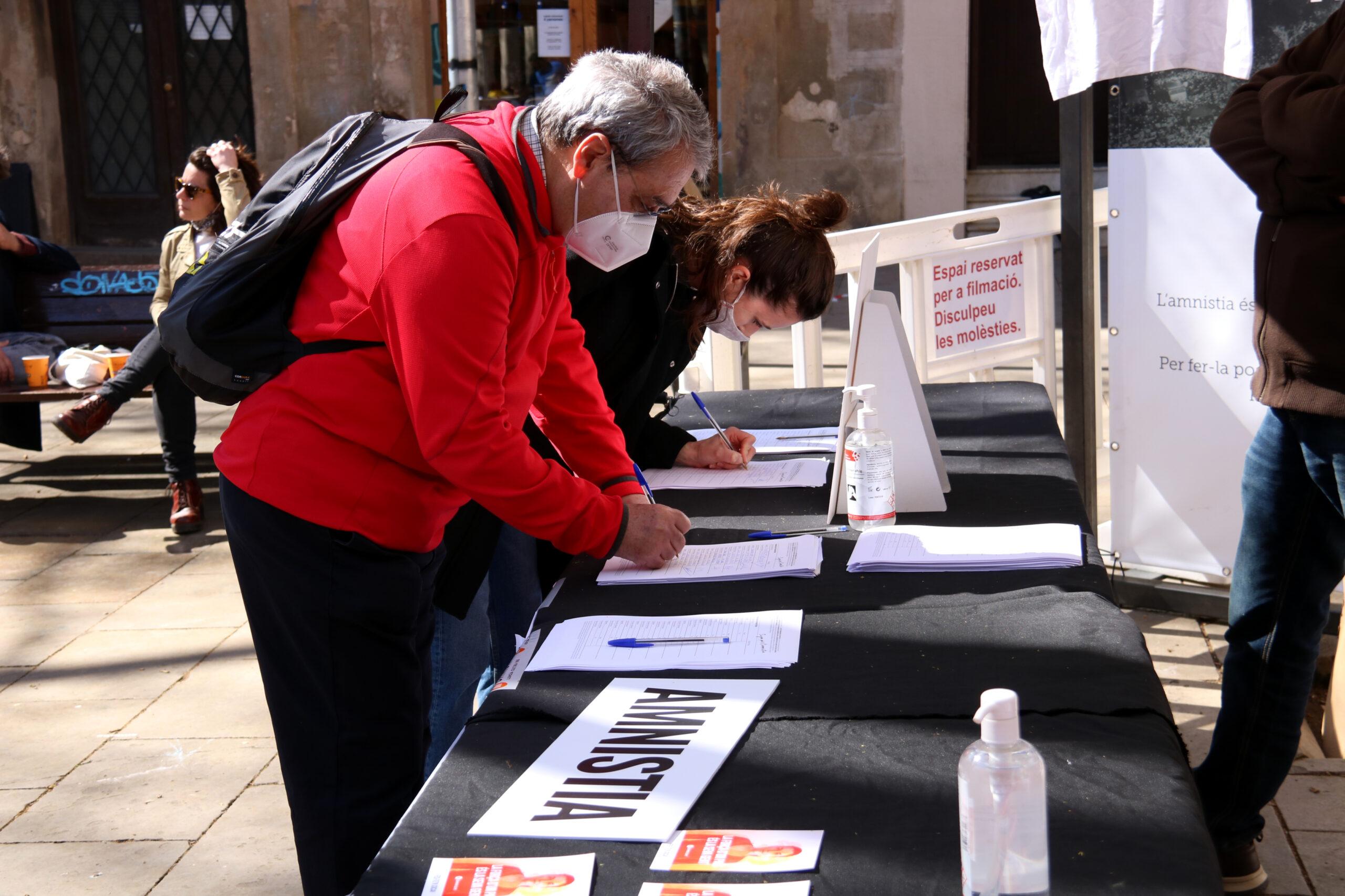 Dues persones signen a favor de la llei d'amnistia, en un acte d'Òmnium a Barcelona (ACN)