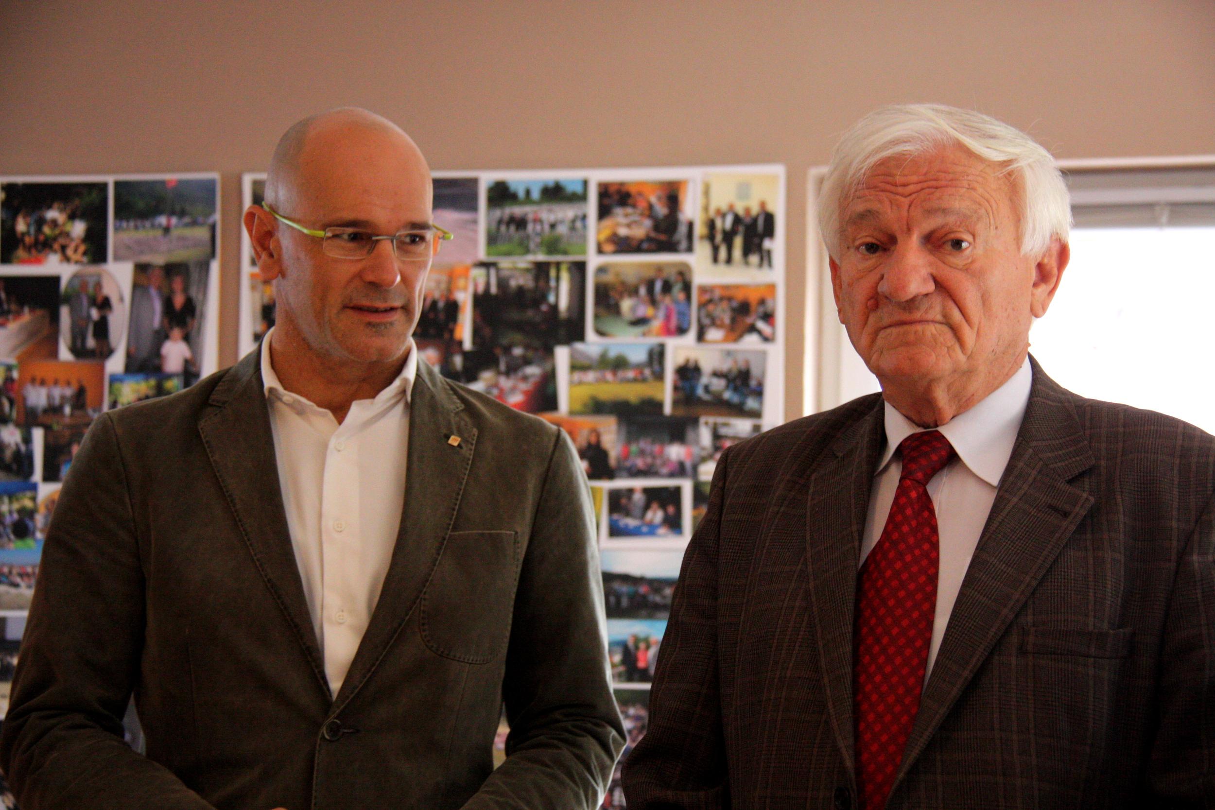 El conseller Raül Romeva amb l'exgeneral Jovan Divjak a la seu de al seva associació d'ajuda a les famílies dels infants víctimes de la guerra, el 13 d'octubre del 2016 / ACN
