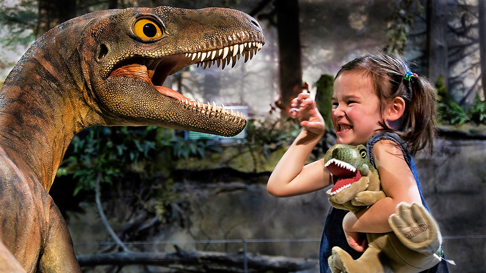 Una nena gaudint amb la reproducció d'un dinosaure | Dinosaurs Tour