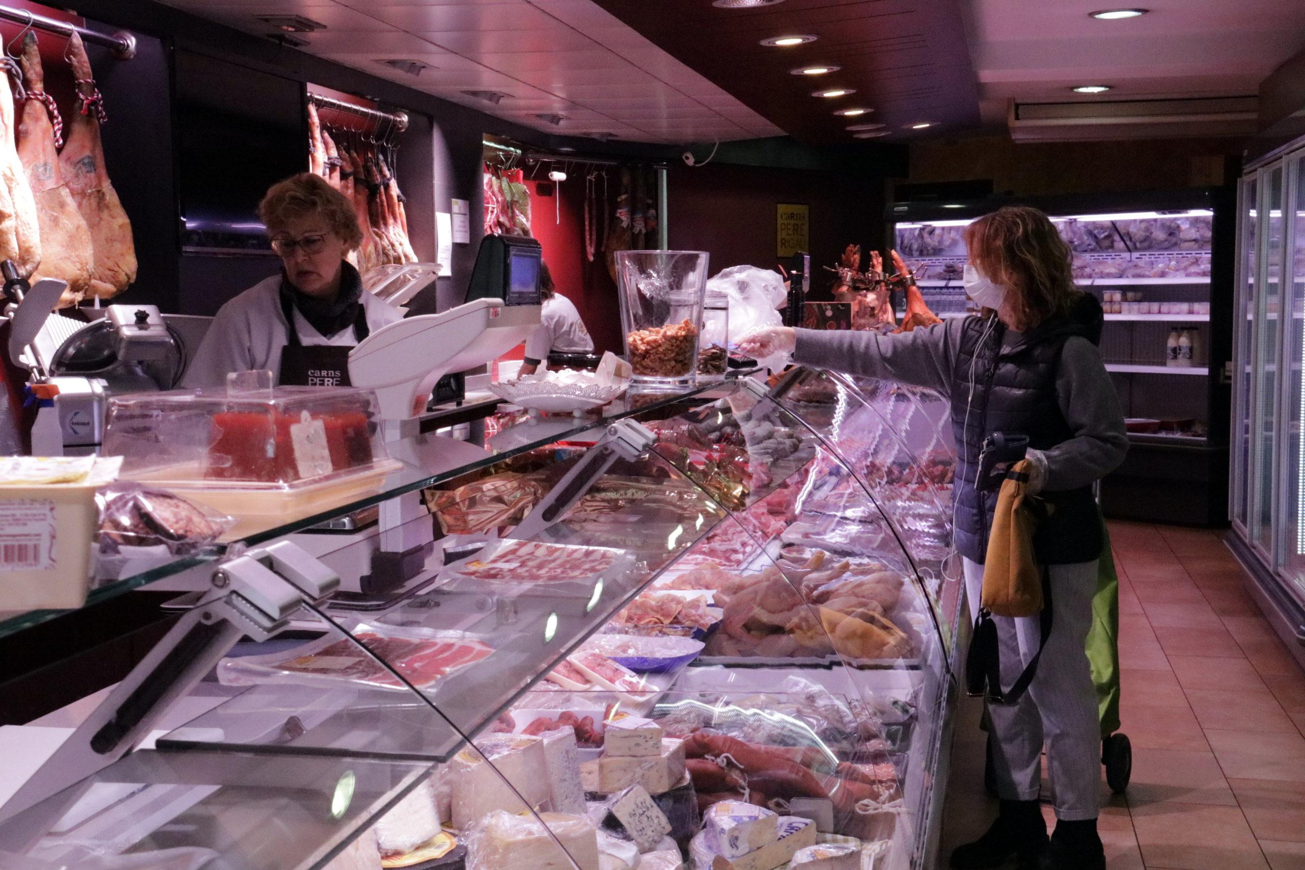 Una clienta amb mascareta a una carnisseria de Girona | ACN