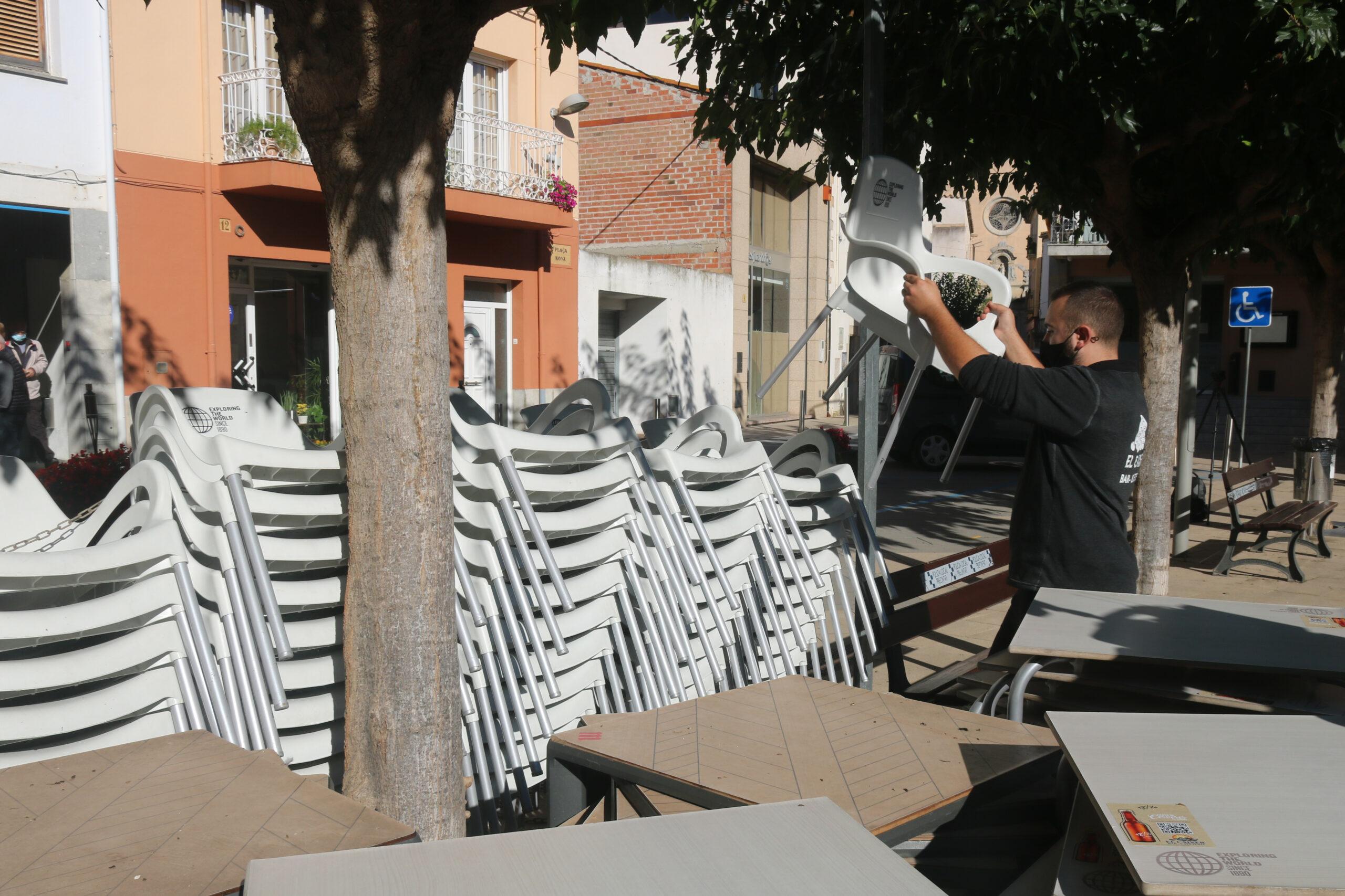 El propietari del bar El Caixer de Vilobí, Jordi López, recollint cadires | ACN