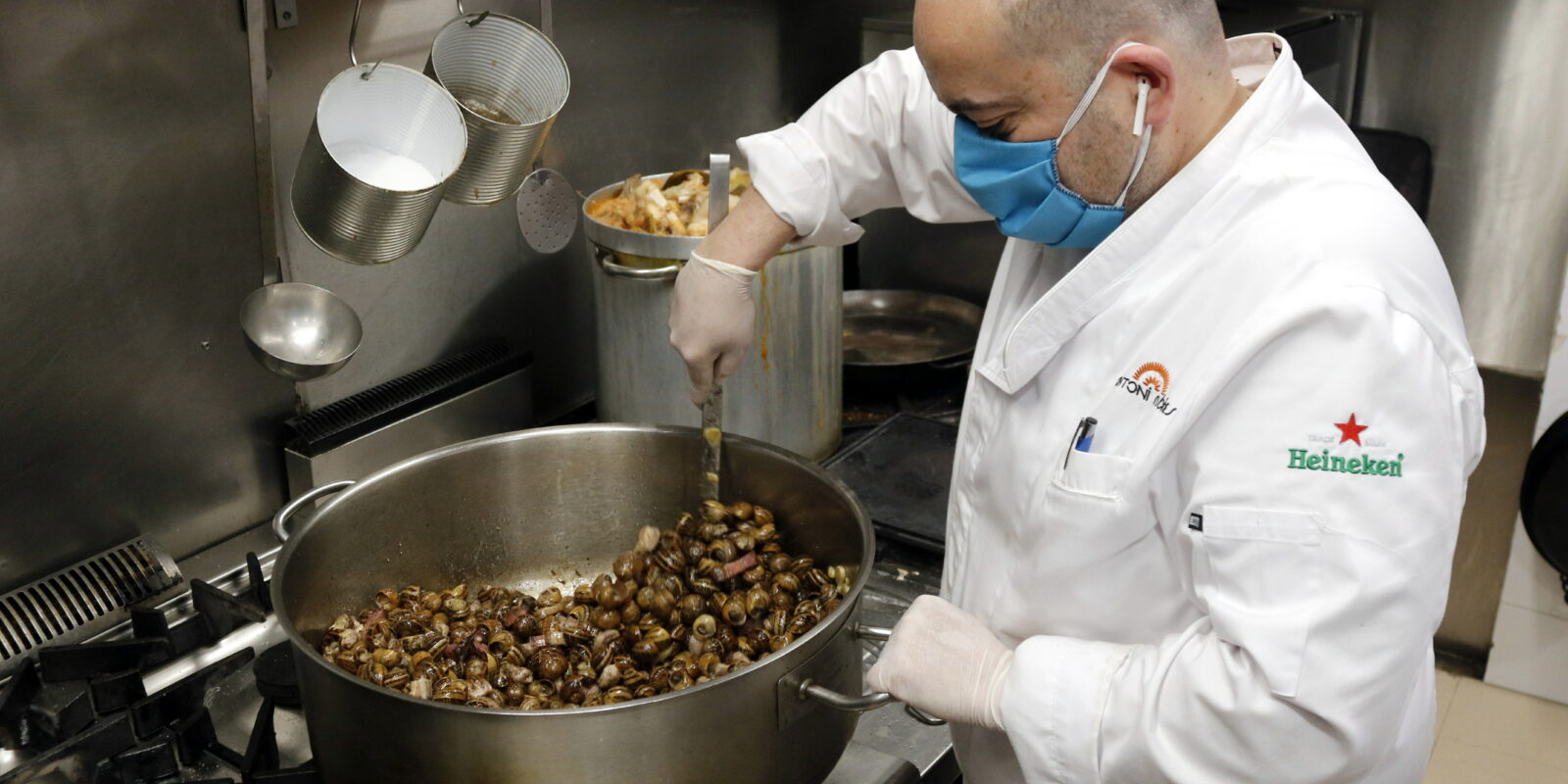 Pla obert d'Antoni Rubies, propietari de l'Arrosseria Antoni Rubies, cuinant caragols a la gormanda, el 10 de maig de 2020. (Horitzontal)