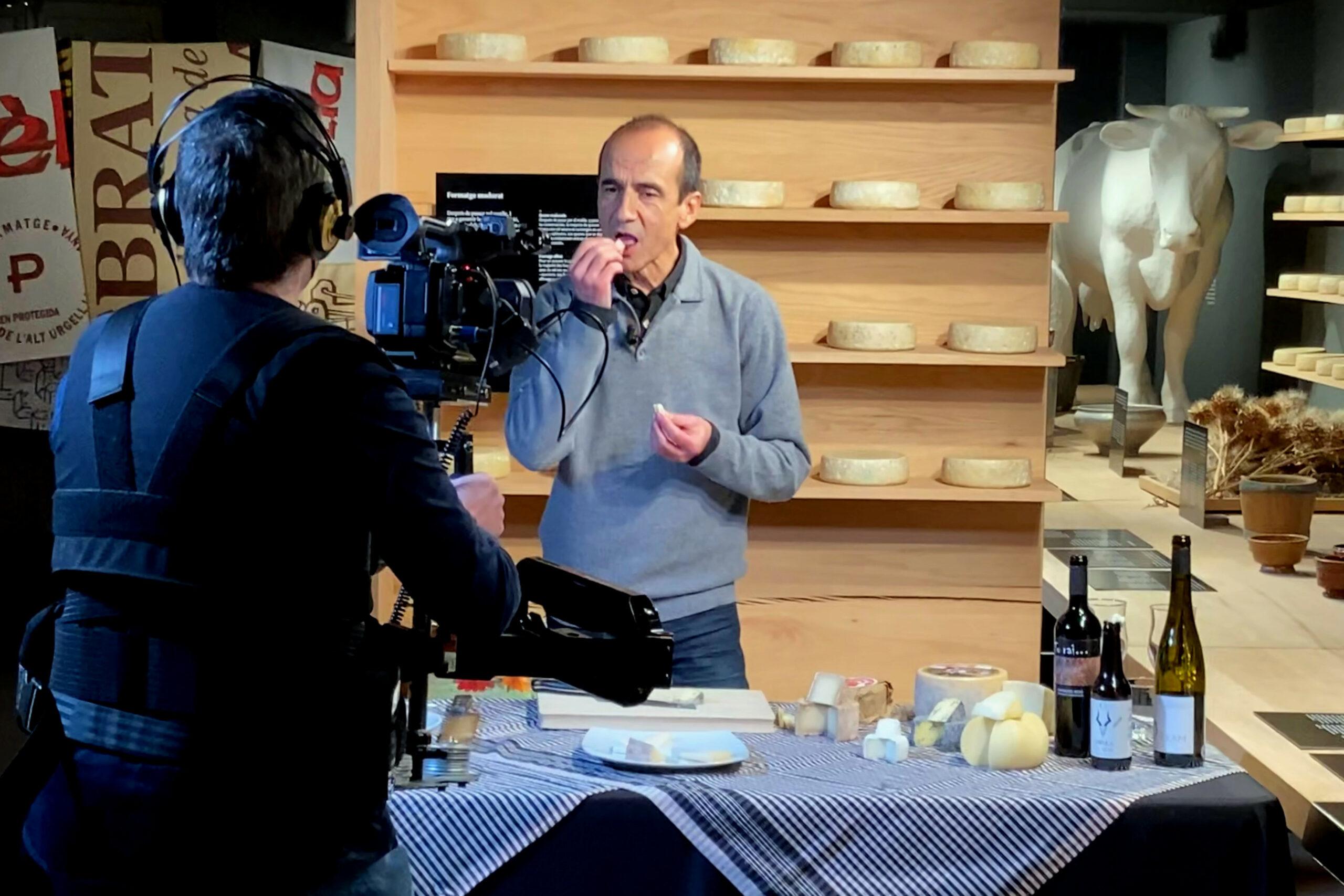 El gastrònom Pep Palau tastant un formatge durant la gravació d'un nou vídeo per al canal virtual de la Fira de Sant Ermengol de la Seu d'Urgell i on es veu també el càmera encarregat de l'audiovisual | ACN