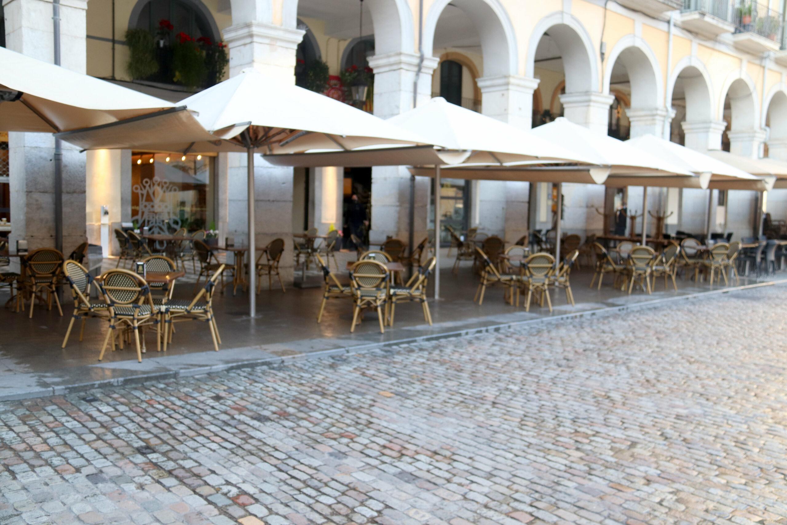 Una de les terrasses de la plaça de la Independència de Girona totalment buida després de la finalització de l'horari d'esmorzars   ACN