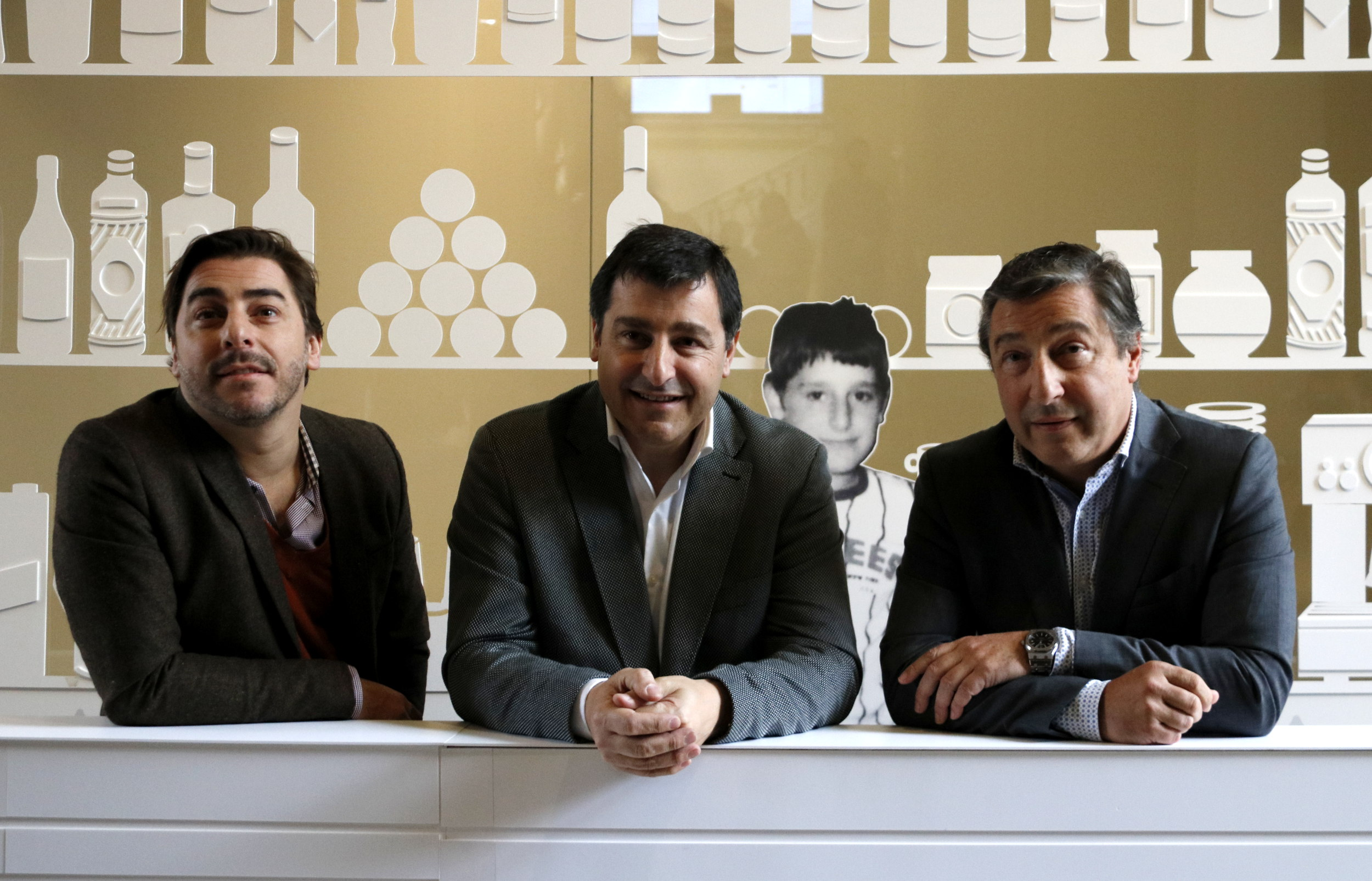 Els tres germans Roca recolzats a la barra d'una recreació del bar familiar, a l'exposició que els hi dedica el Palau Robert | ACN