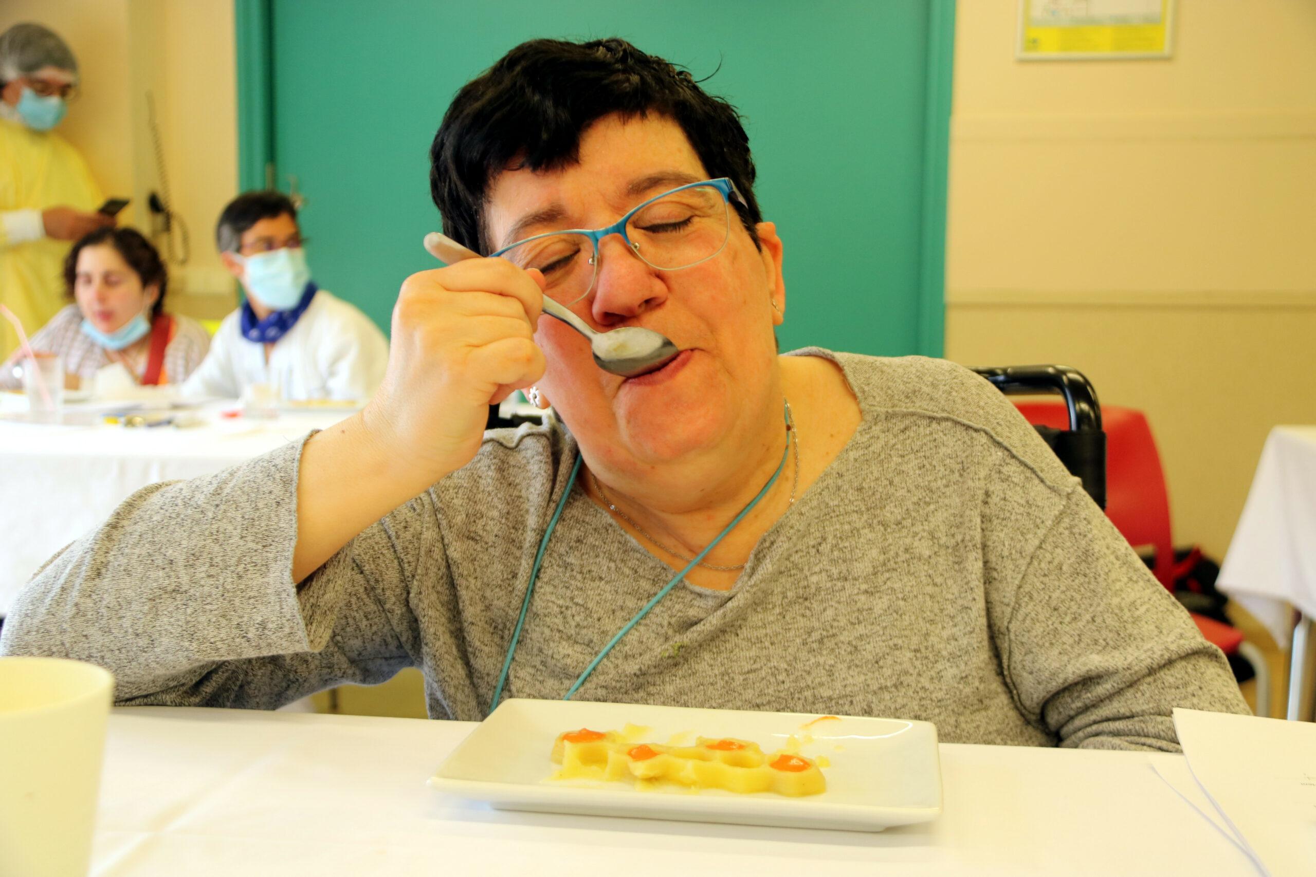 Pla mitjà de la Judit, una de les usuàries del centre de disminuïts físics, tasta un plat de patates braves fet a partir de la tecnologia 3D   ACN