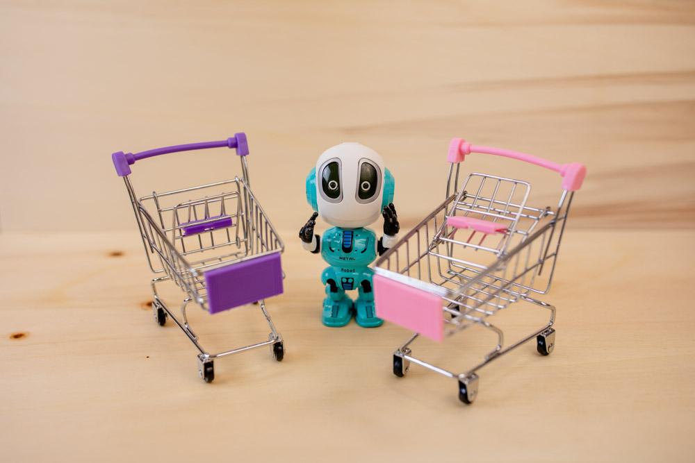 Zwei Einkaufswagen und dazwischen steht ein Roboter - alles Spielzeuge - auf Holzuntergrund